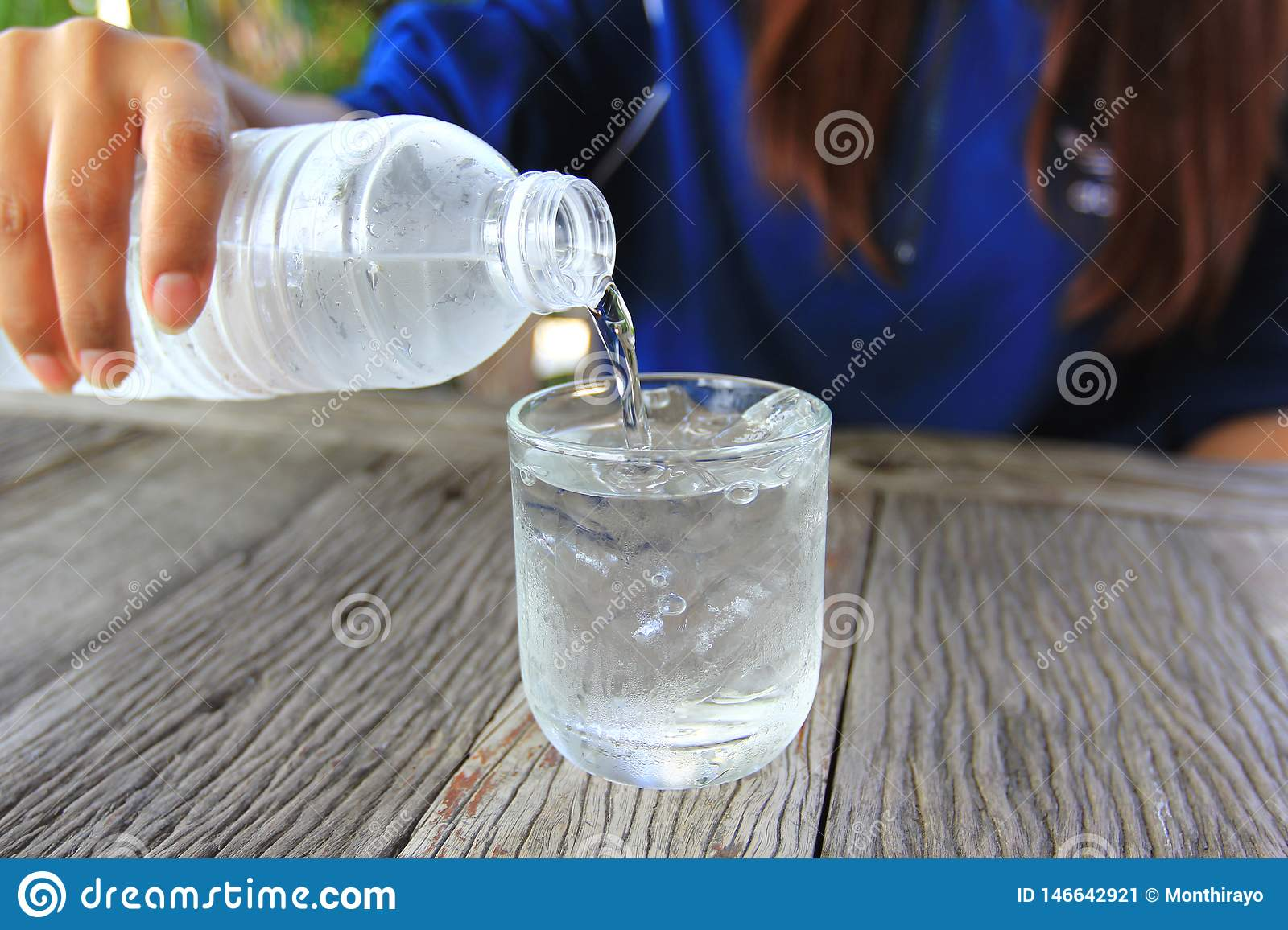 Closeup of young woman pouring water from a plastic bottle into glass on table in restaurant