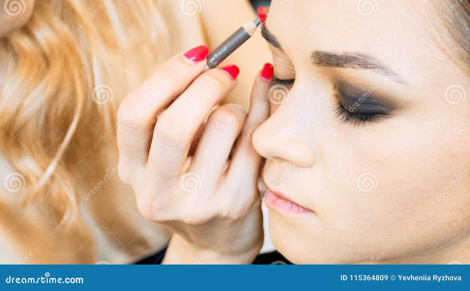 Closeupbild av ögonbryn för ` s för modell för målning för makeupkonstnär med att dra upp konturerna av blyertspennan