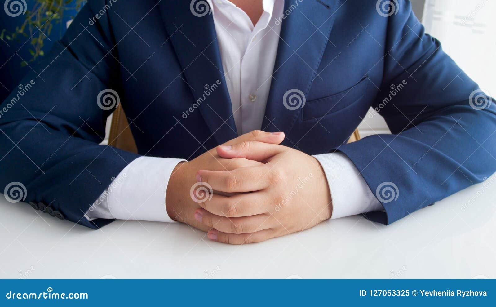 Closeupbild av affärsmannen i blåttdräkt med vikta händer som sitter bak det vita träkontorsskrivbordet