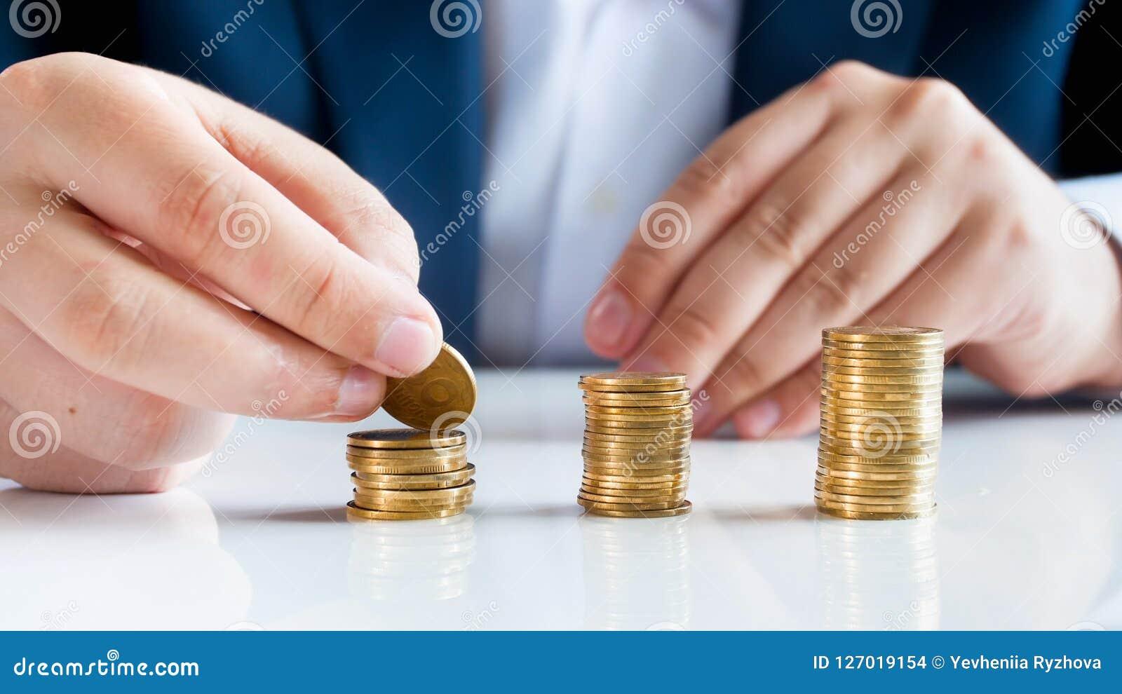 Closeupbild av den manliga bankiren som sätter guld- mynt i höjdpunktbuntar på kontorsskrivbordet