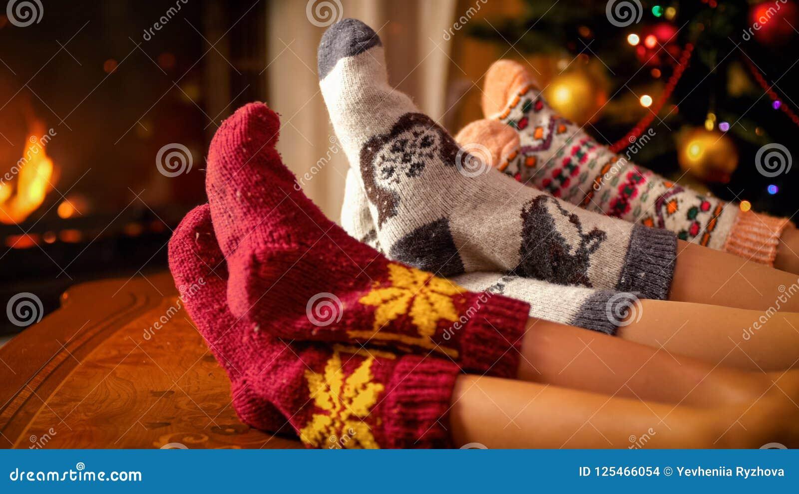 Closeupbild av familjen i varma stack sockor som ligger bredvid spisen och julgranen