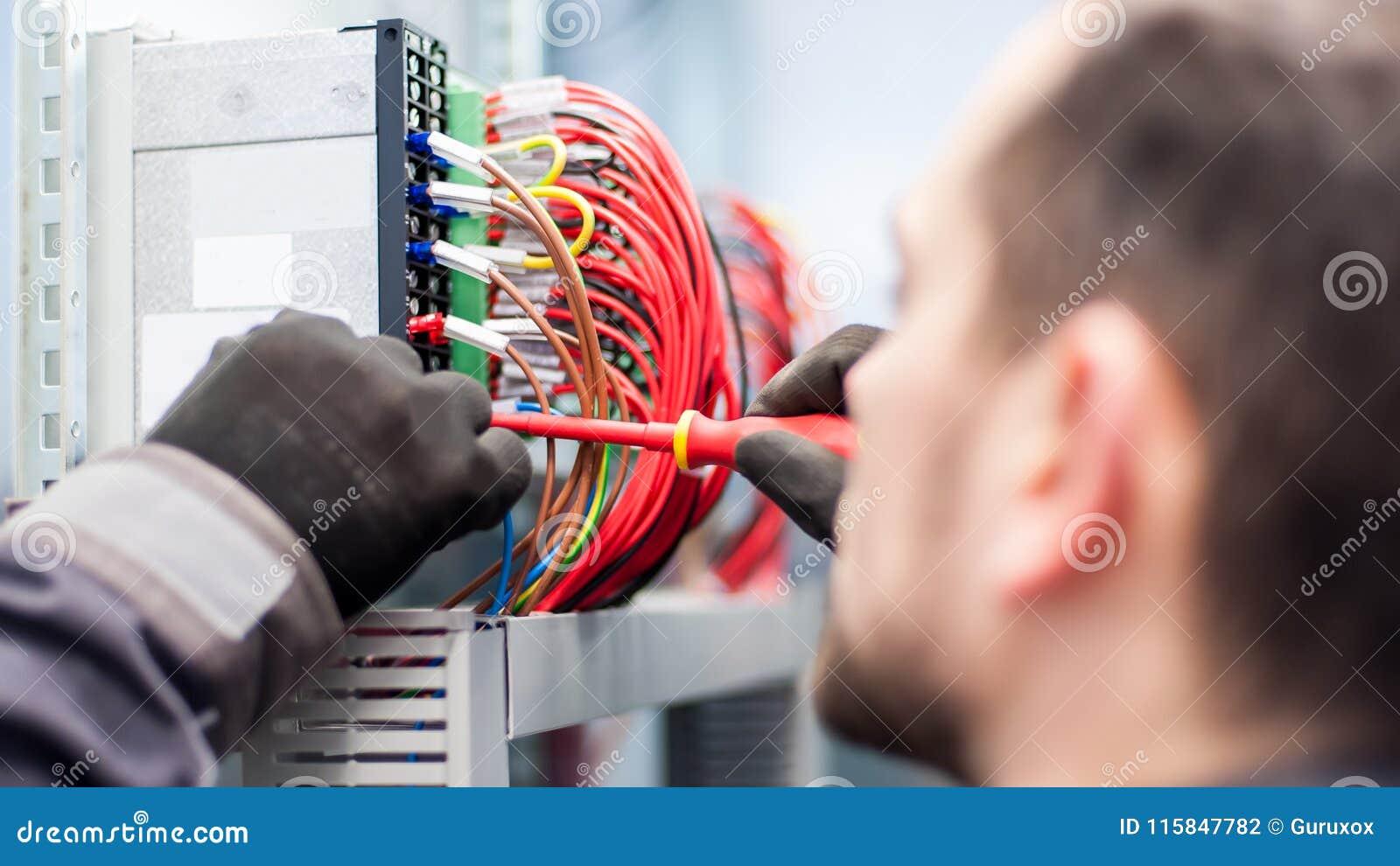 Closeupen av elektrikerteknikern arbetar med trådar för elektrisk kabel