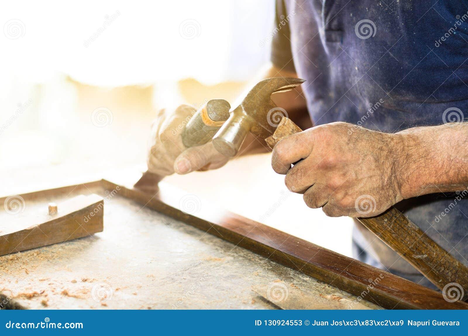 Closeupen av en snickare räcker arbete med en stämjärn och en hammare på träarbetsbänken