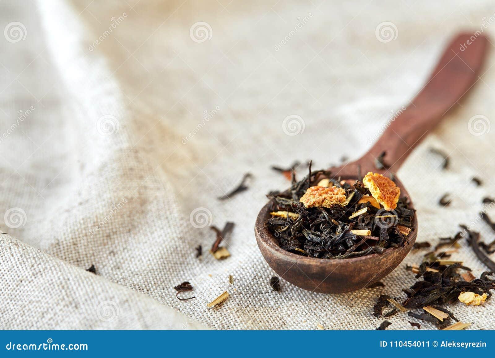 Closeupen av en träsked fyllde med spridda teblad, grunt djup av fältet, bästa sikt