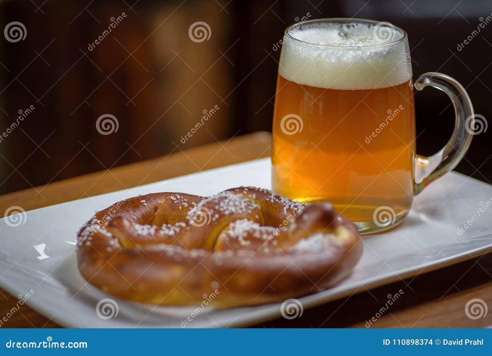 Closeupen av ett stort exponeringsglas rånar av öl och en mjuk kringla