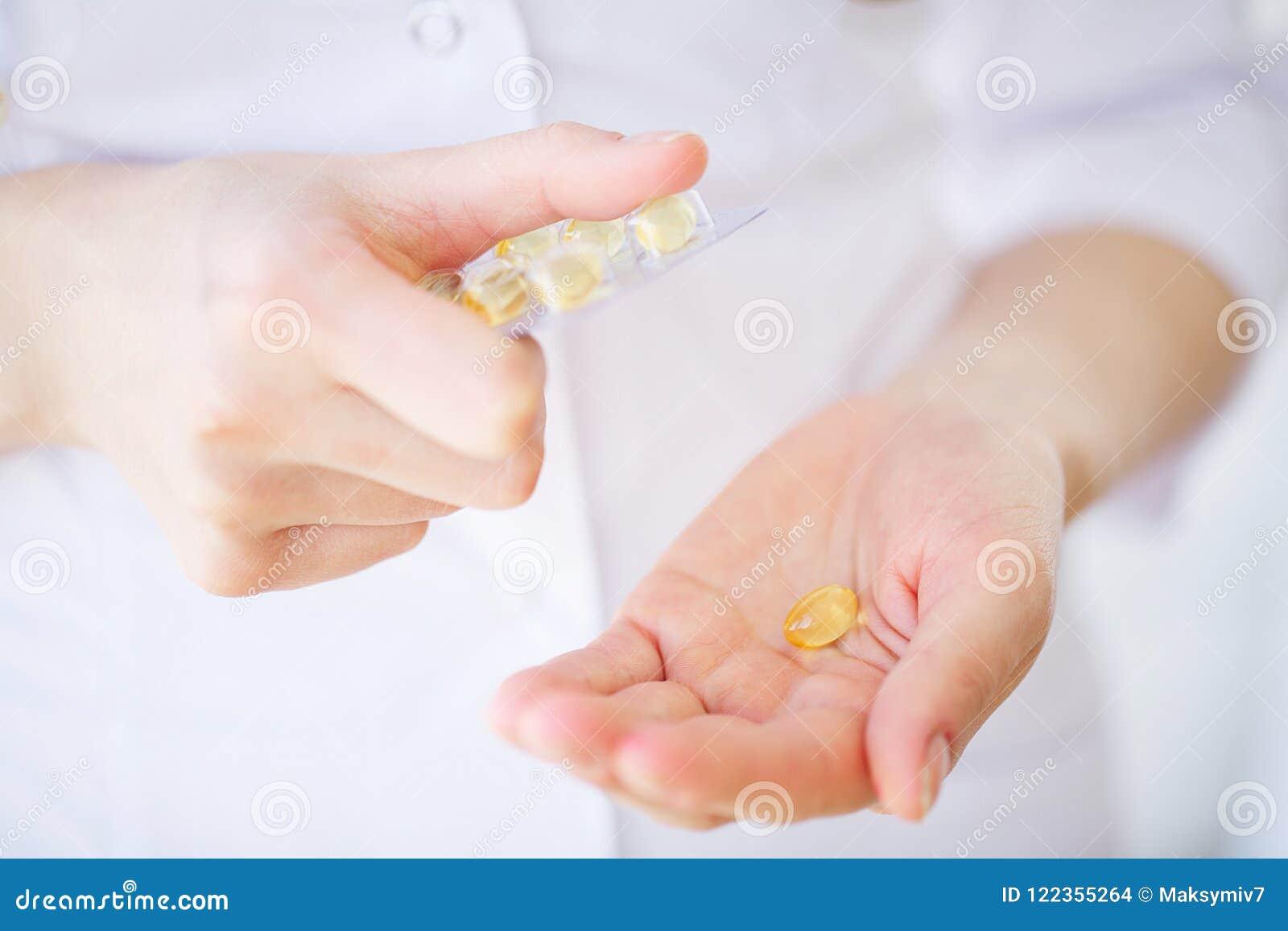Closeupen av kvinnan räcker hållande variation av färgrika vitaminpreventivpillerar