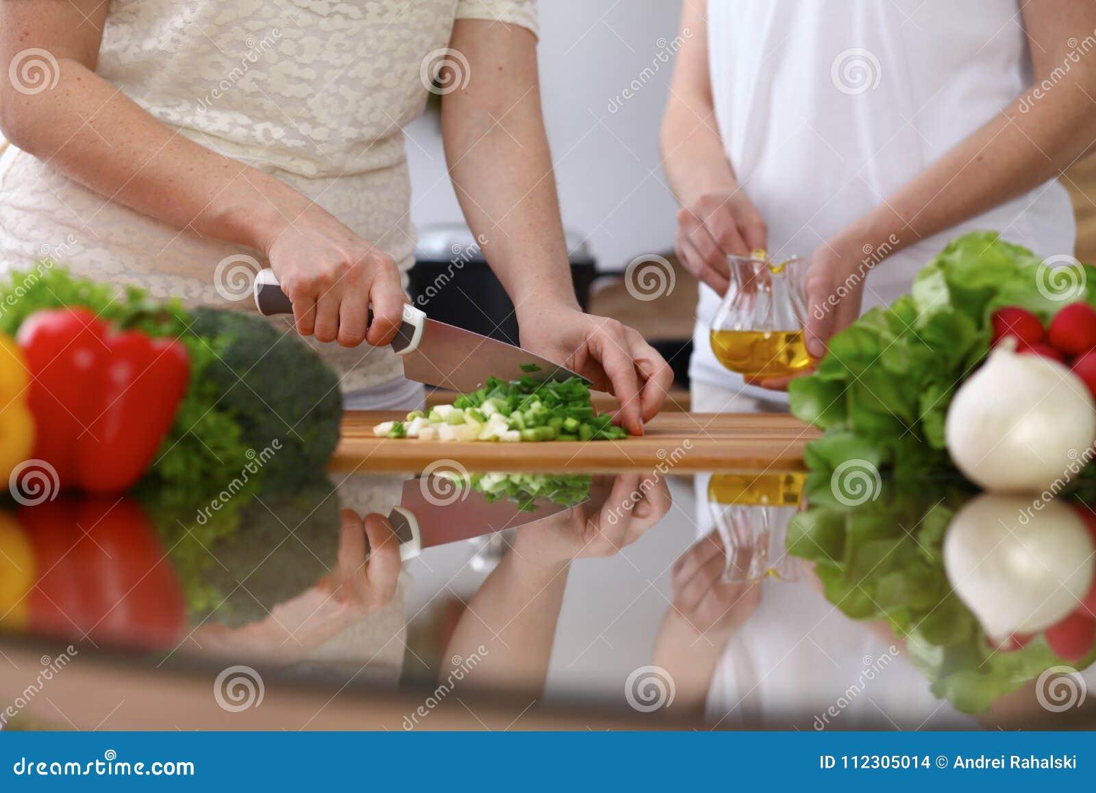 Closeupen av människan räcker matlagning i kök Bitande salladslök för moder och för dotter eller för två kvinnlig för sallad sunt