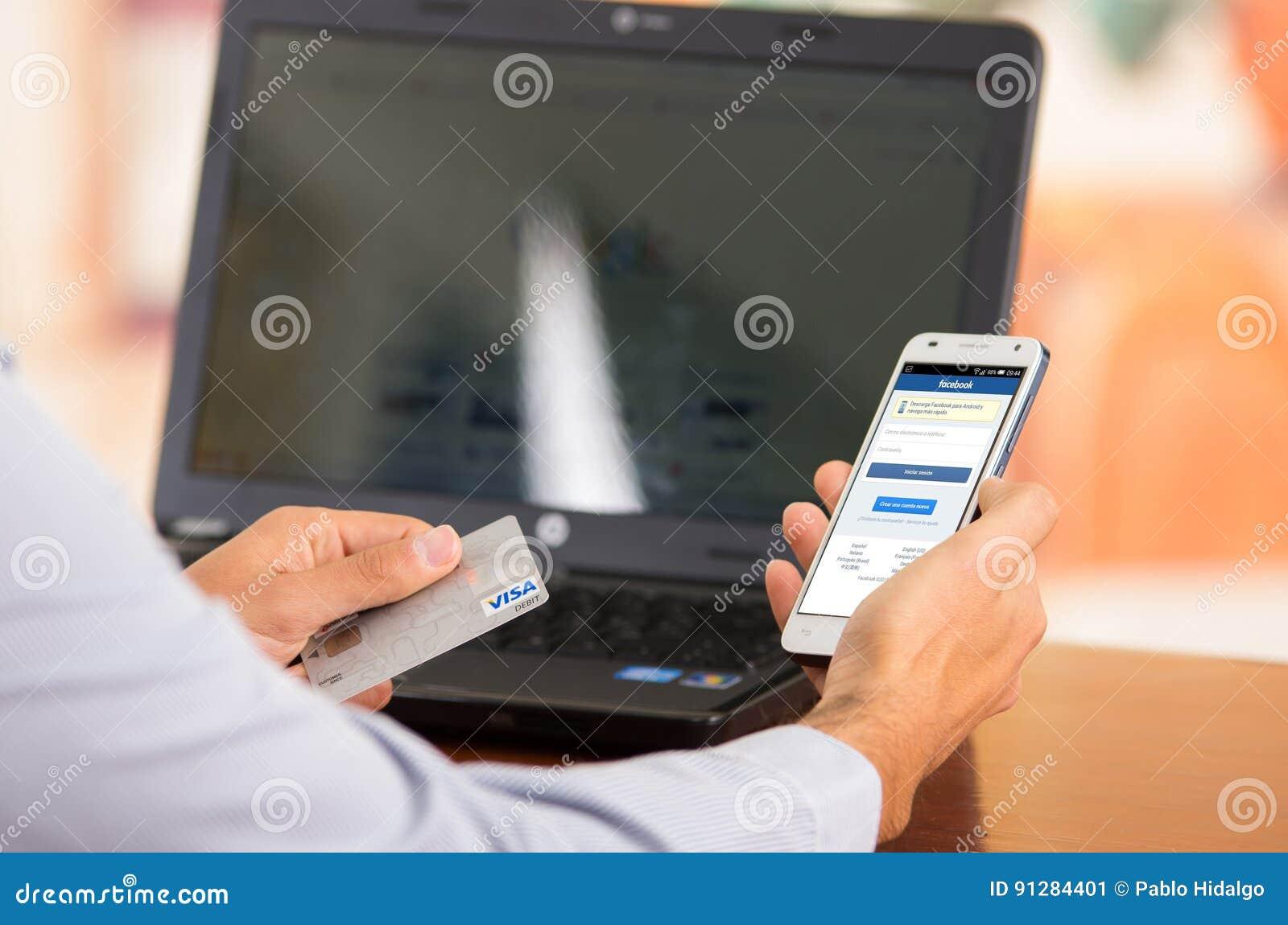 Closeupen av ungt mans händer som rymmer upp smartphonen med den Facebook websiten synlig, visumkortet i annan hand med bärbara d