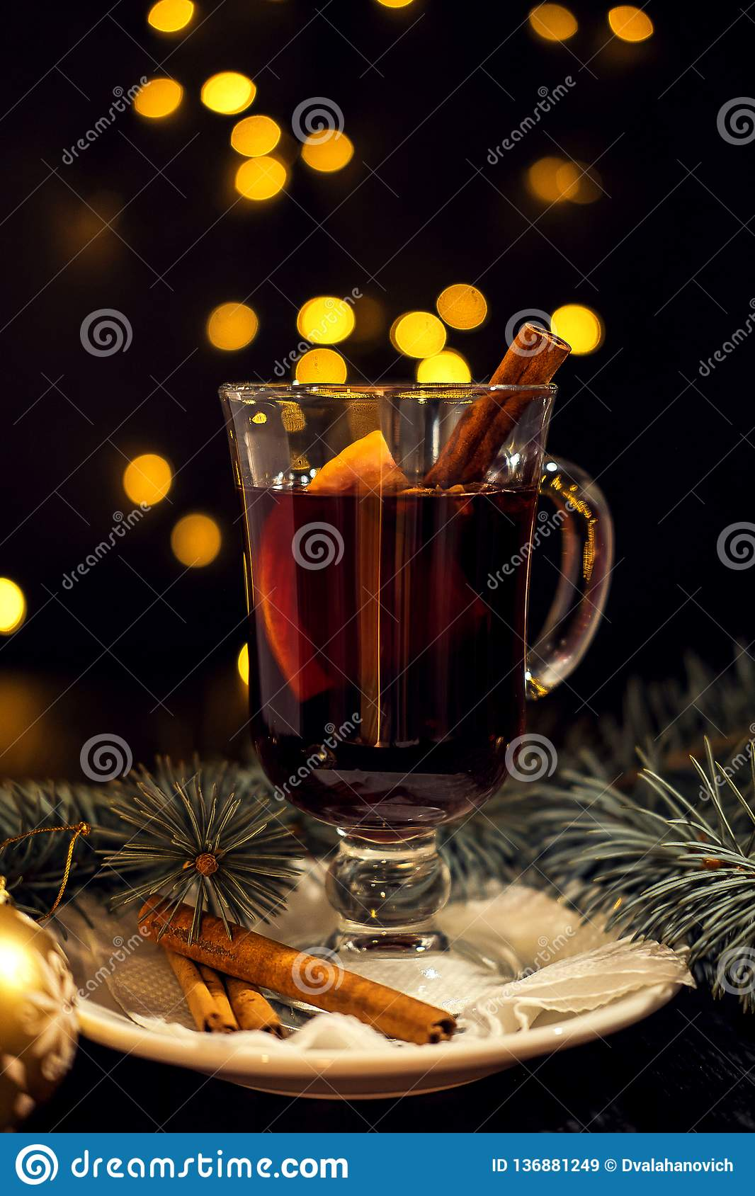Closeupexponeringsglas av funderat vin med orange och kanelbrunt på den vita plattan, julljus