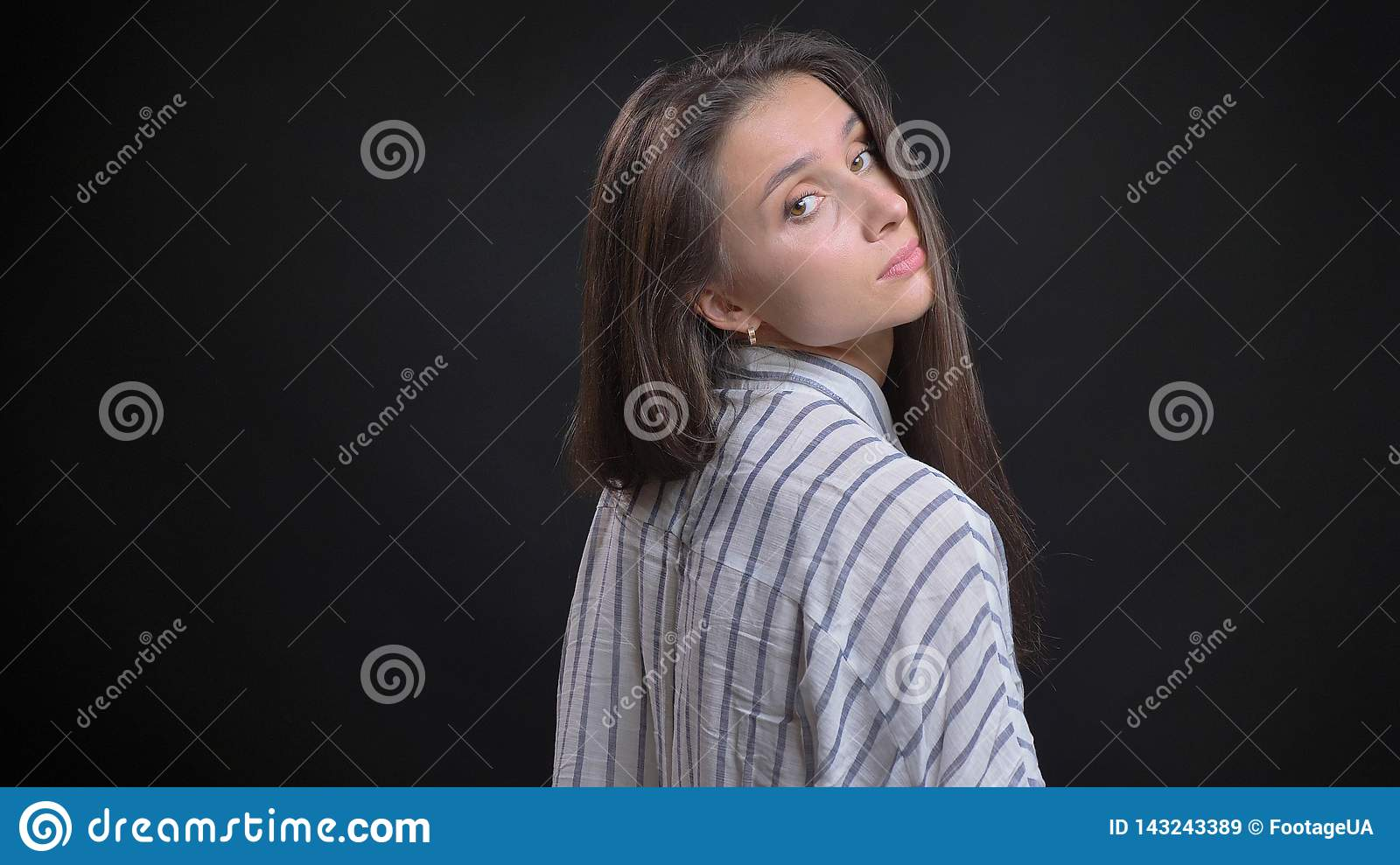 Closeupfors av den unga attraktiva caucasian kvinnliga modemodellen som poserar från den tillbaka sikten med isolerad bakgrund
