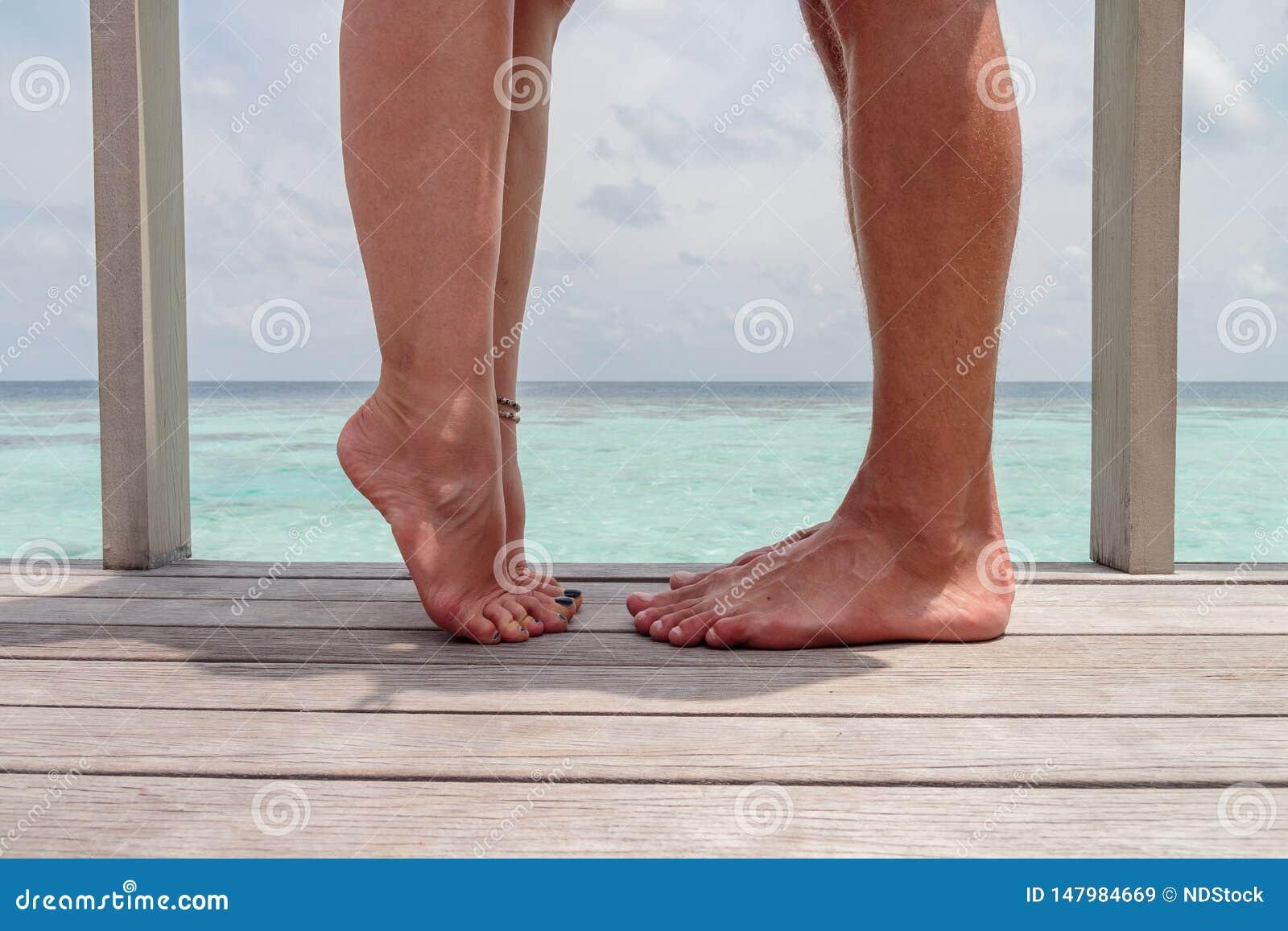 Closeupfoto av kvinna- och manben, flicka med det lyftta benet Par som kysser, över havsbakgrund, honom vs henne