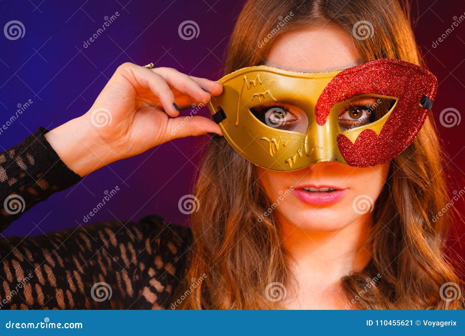 Closeupkvinnaframsida med den guld- röda maskeringen för karneval på mörker