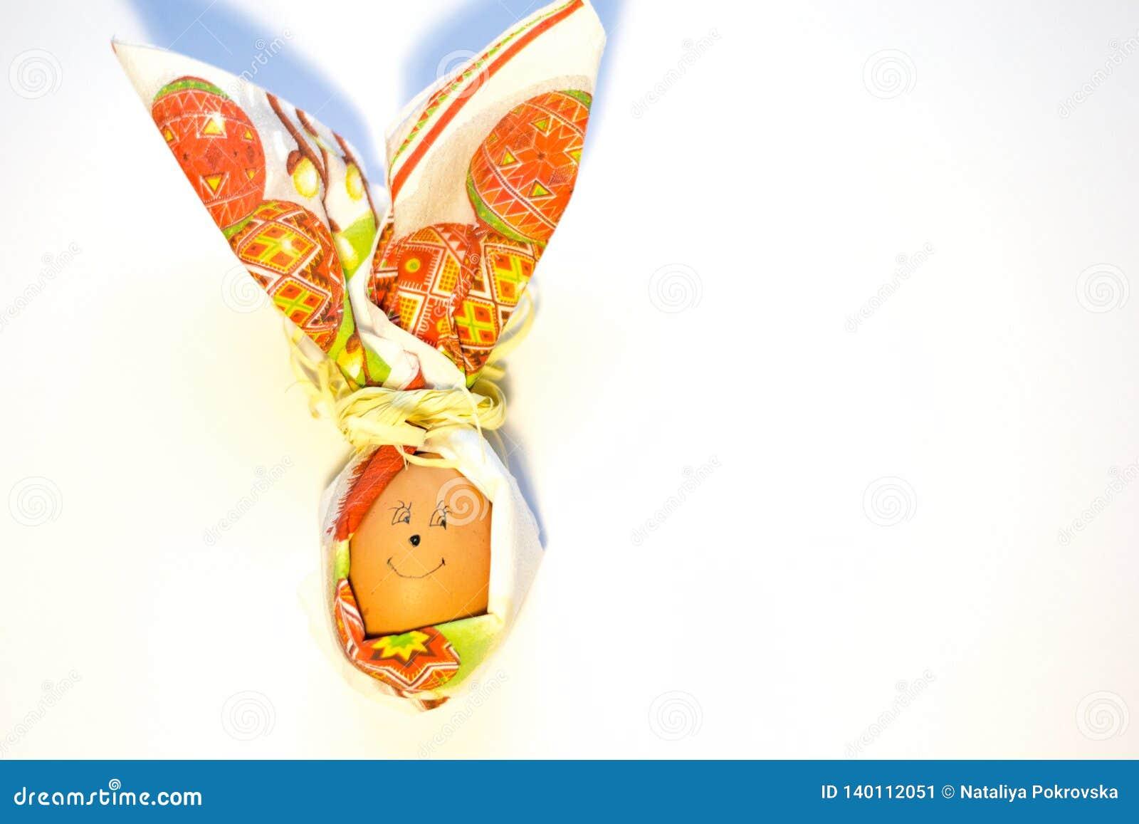 Closeuppåskägg med vänt mot leende i form av kanin av pappersservetten som isoleras på vit bakgrund Förberedelse för vår