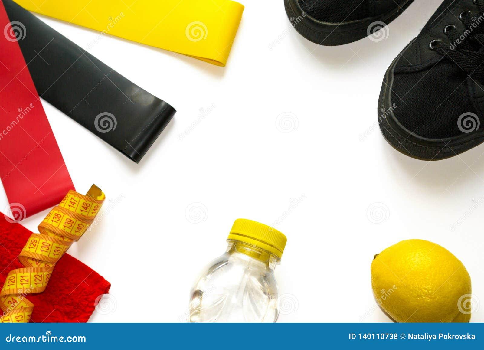 Closeupram av sportutrustning för exersises i idrottshallen för kvinnor på vit bakgrund med copyspace Elastiska konditionexpander