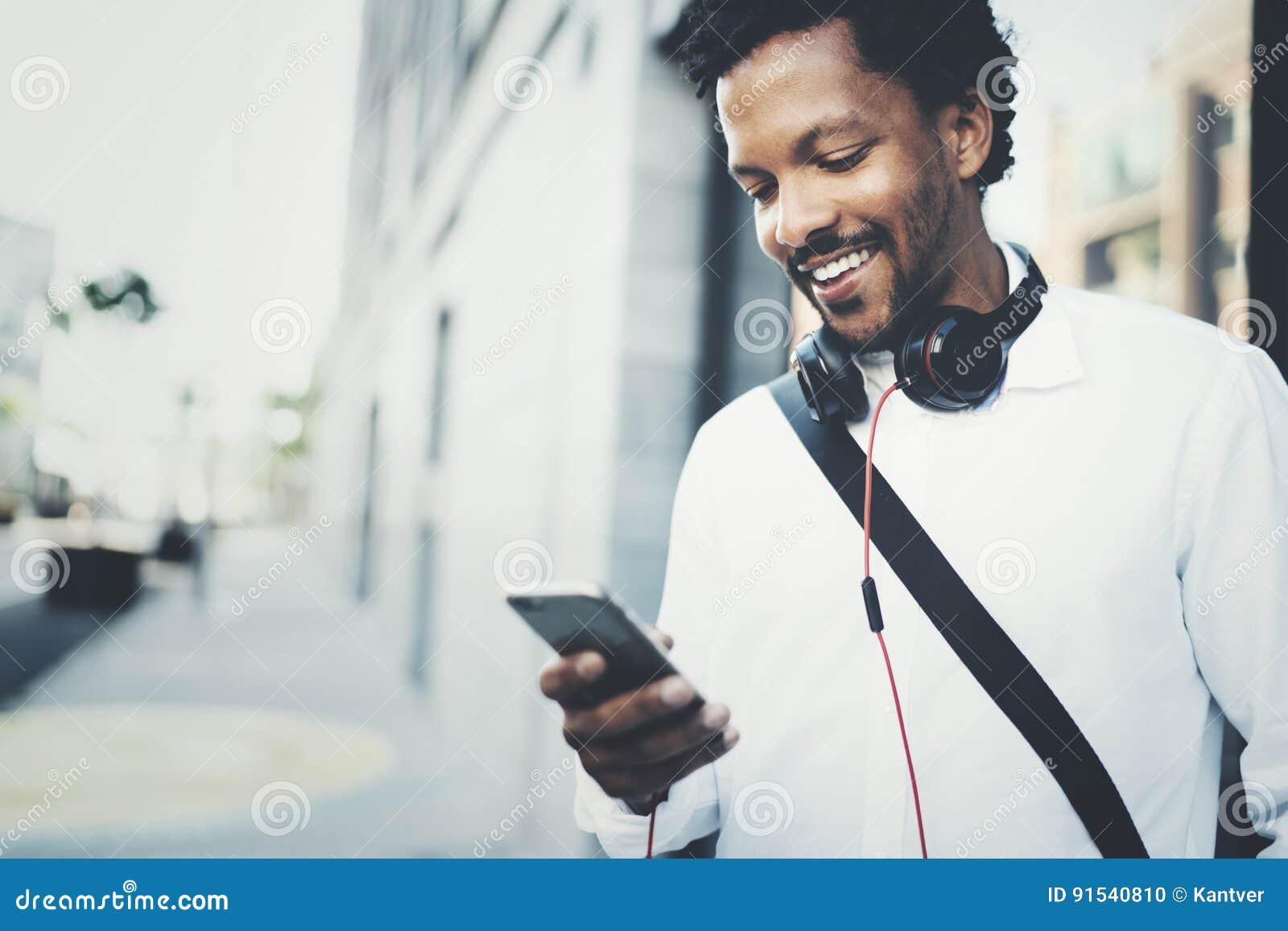 Closeupsikt av den lyckliga le afrikanska mannen som använder den utomhus- smartphonen Ståenden av barn svärtar gladlynt smsa för