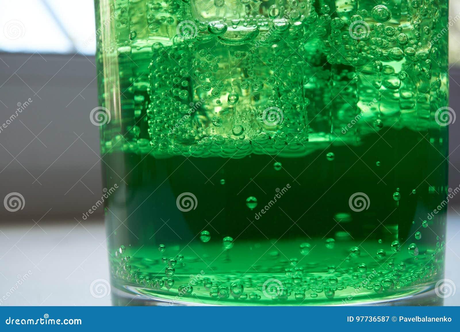 Closeupskott av ett grönt kolsyrat vatten