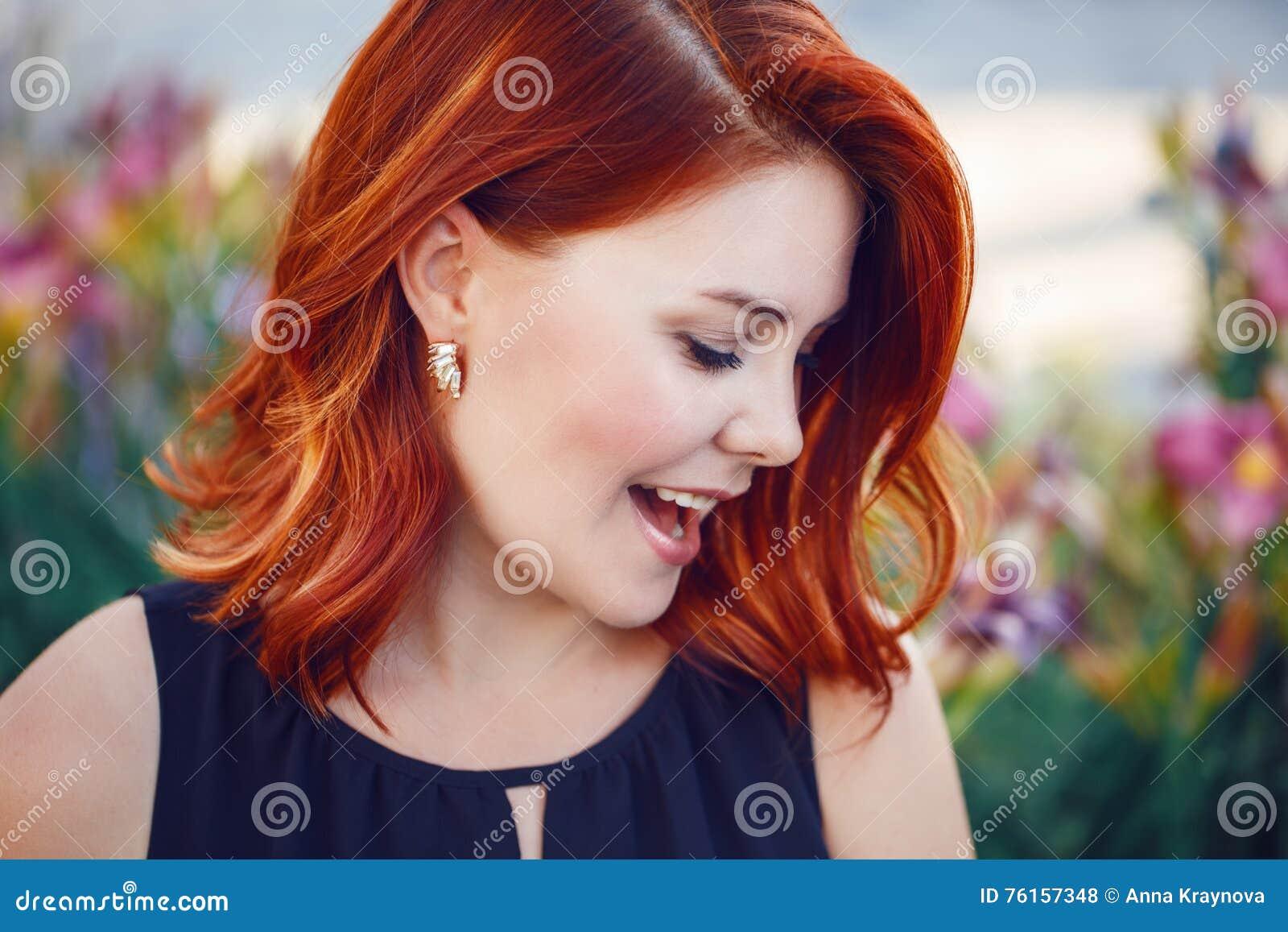 Closeupstående av att le den skratta flirty mitt åldrades vita caucasian kvinnan med vinkat lockigt rött hår i svart klänning
