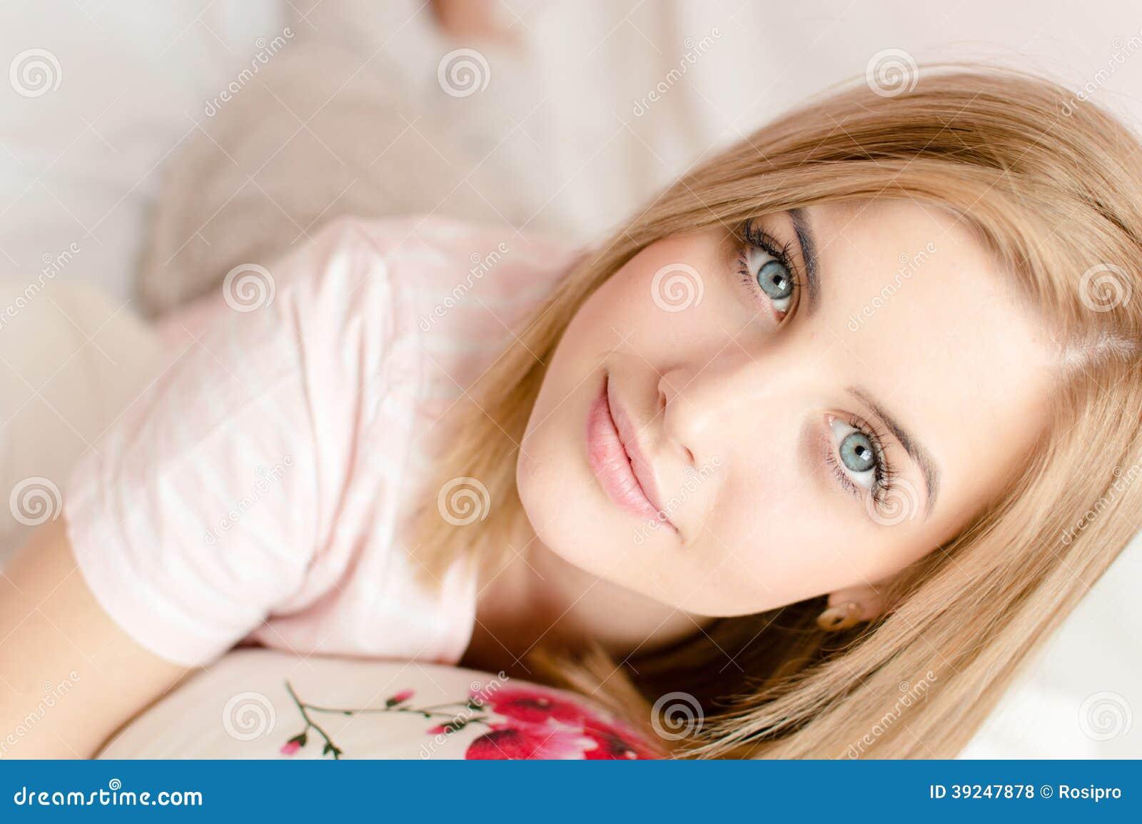 Closeupstående av den attraktiva härliga unga blonda kvinnan med blåa ögon och utmärkt hud, i säng & att se kameran