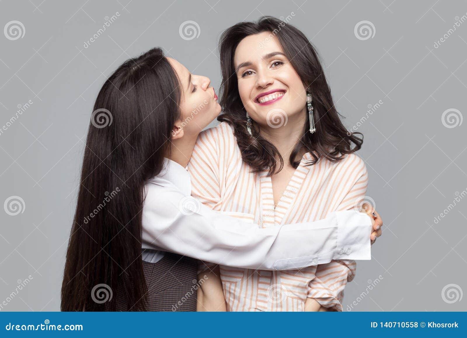 Closeupstående av den härliga långa haired brunettflickan som kramar och att försöka att kyssa hennes bästa vän eller syster och