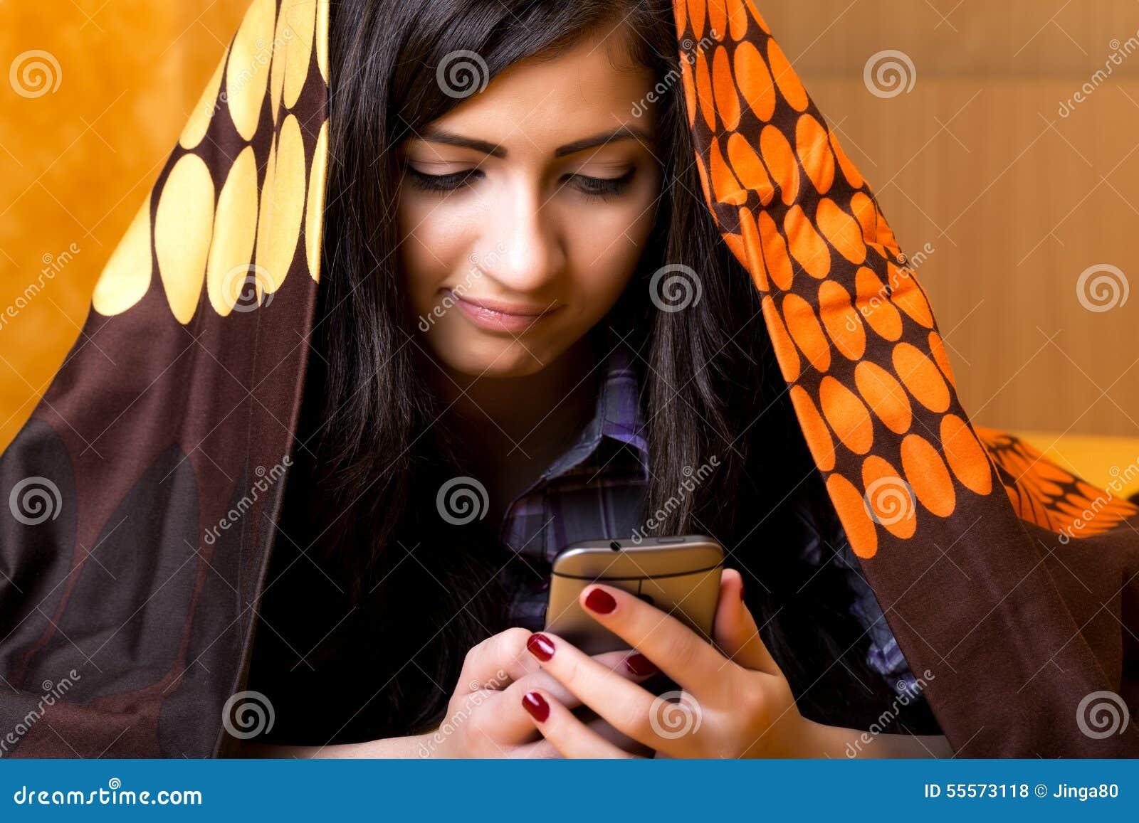 Closeupstående av den härliga tonårs- flickan som använder den dolde mobil telefonen