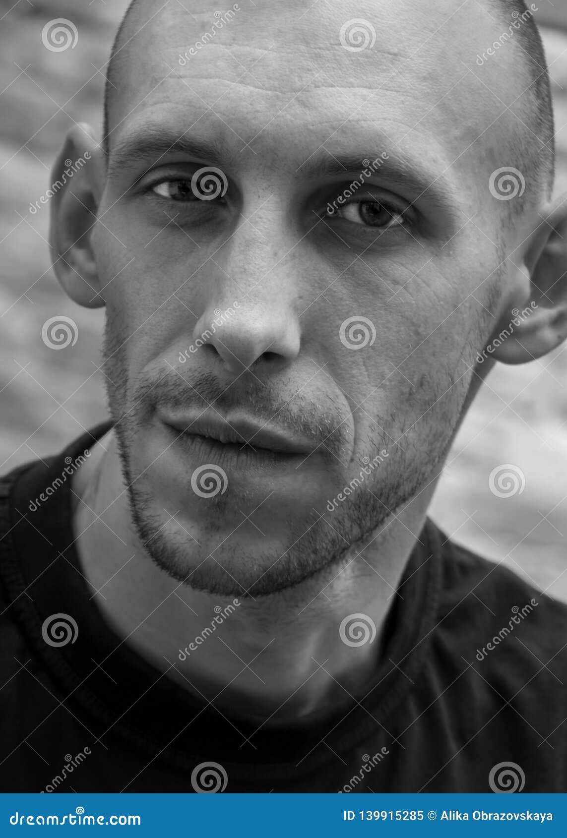 Closeupstående av en skallig man med ett leende och ett brutalt utseende i svartvitt