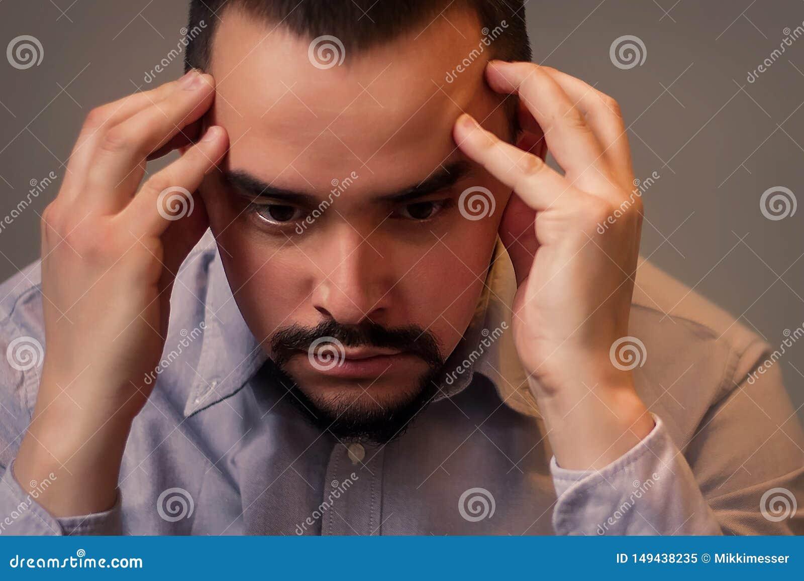 Closeupst?ende av en stressad medel?lders man i den gr?a skjortan som inomhus sitter med den ledsna framsidan och t?nker rymma hu