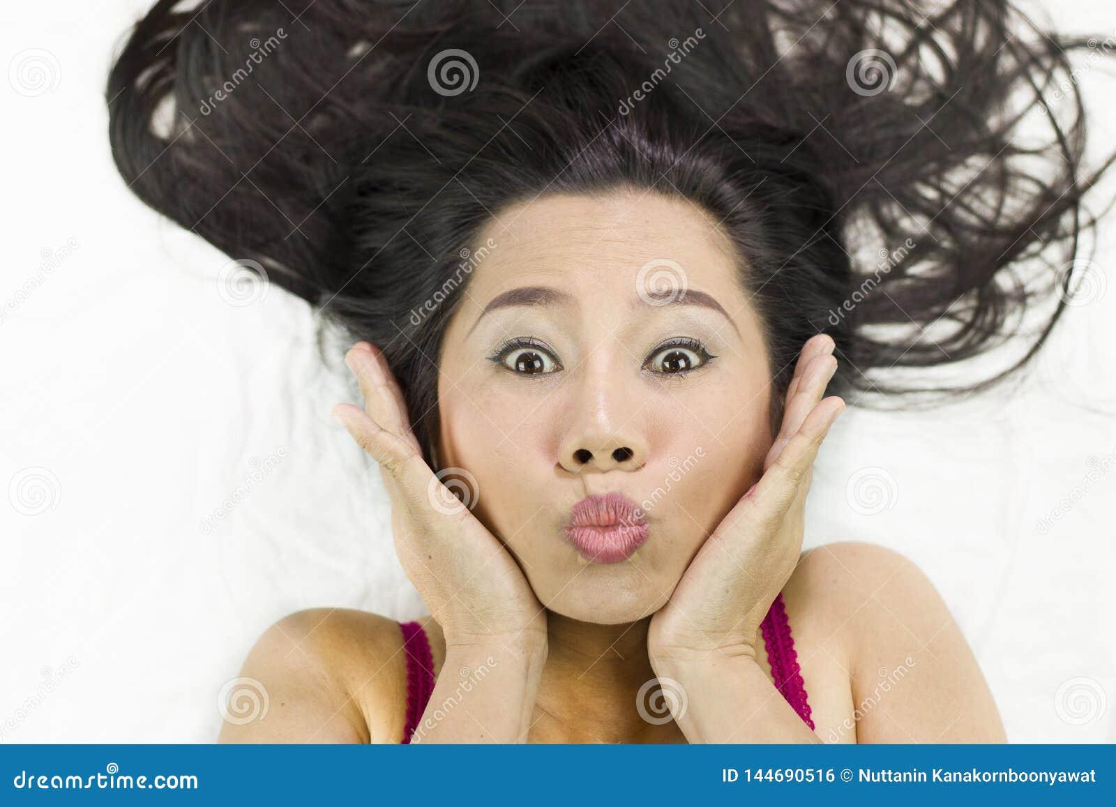Closeupstående av lyckliga asiatiska kvinnor som ligger på jordning med svart långt hår tillförordnat leende, gyckel
