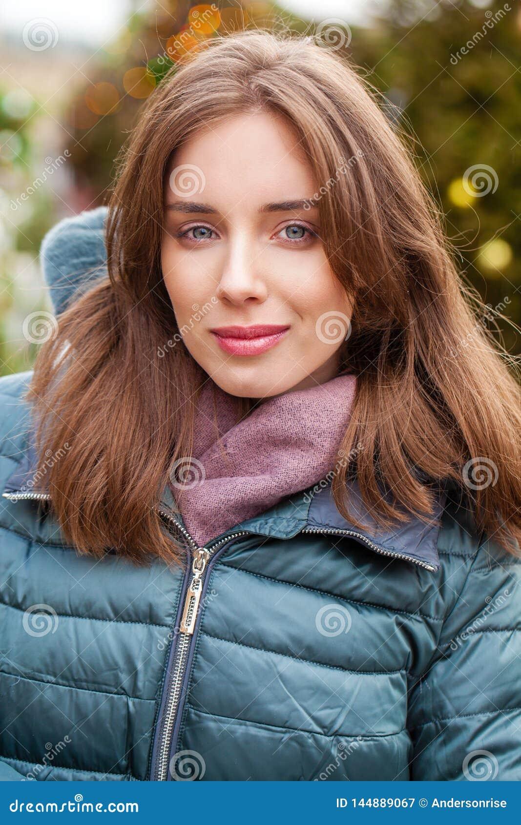 Closeupst?ende av en ung kvinna i vintern ner omslaget