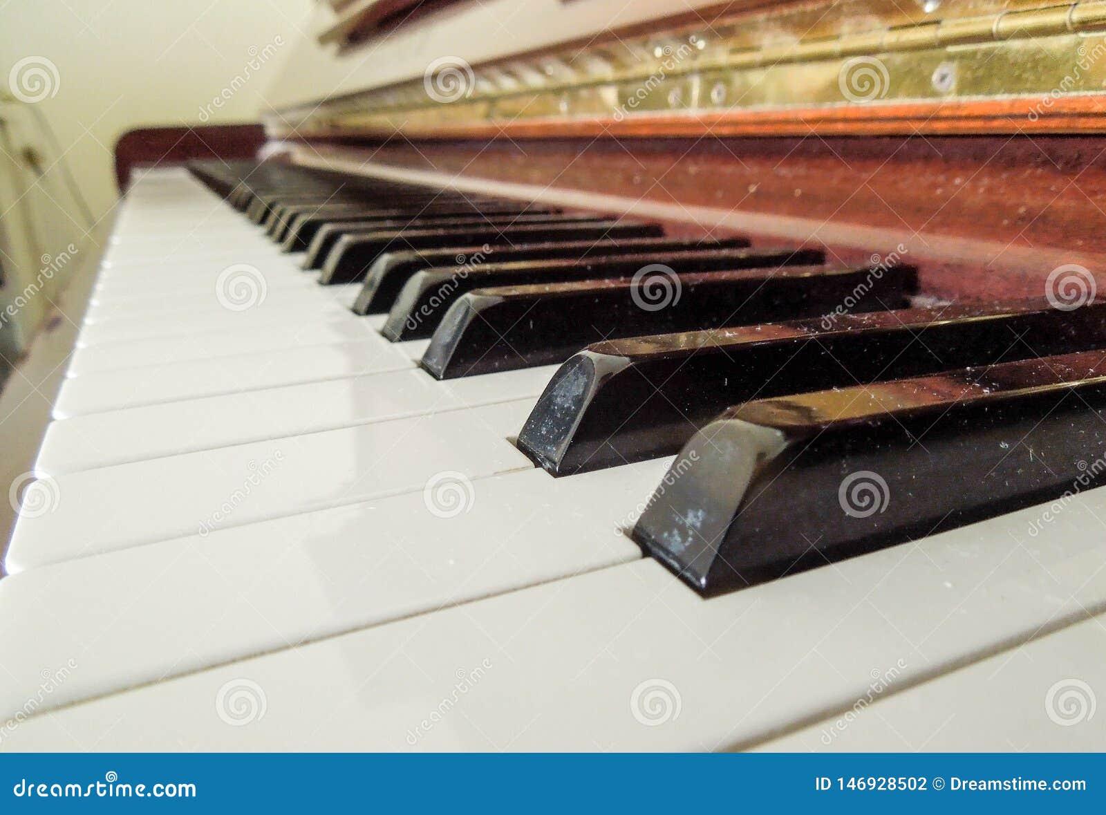 Closup de um piano de madeira com duas chaves pretas no foco