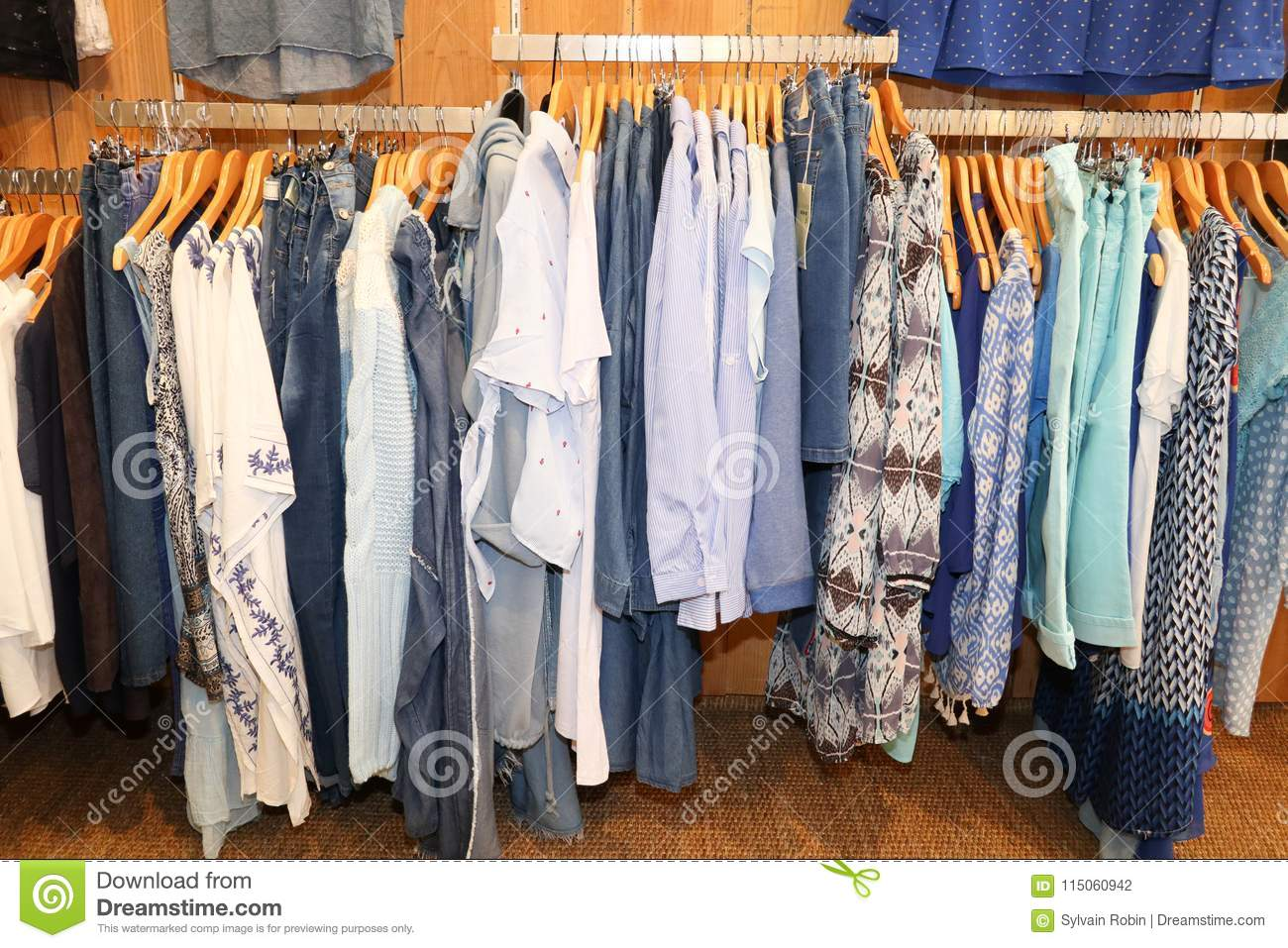 7bf41e5ee Cloth on clothes rail in clothing store Colorful women dresses on hangers  in a retail shop