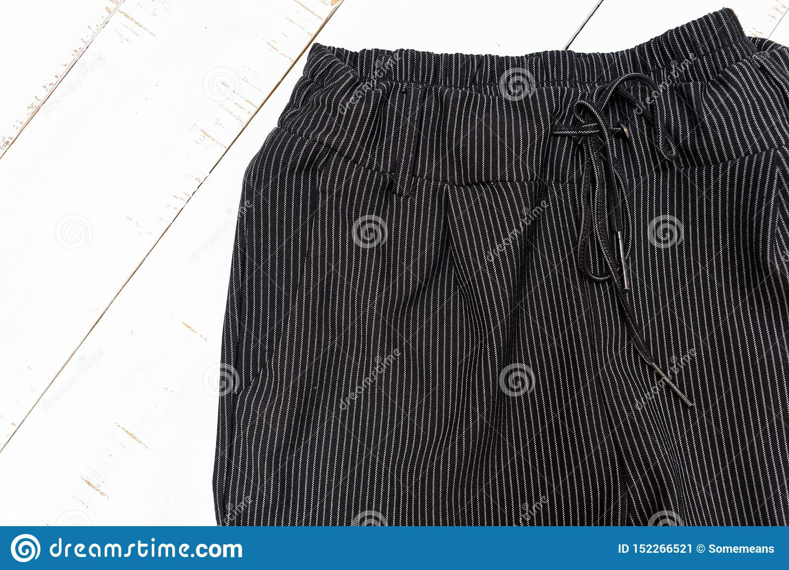 Clothes fashion concept. Detail of black trousers on white wooden background. Top view