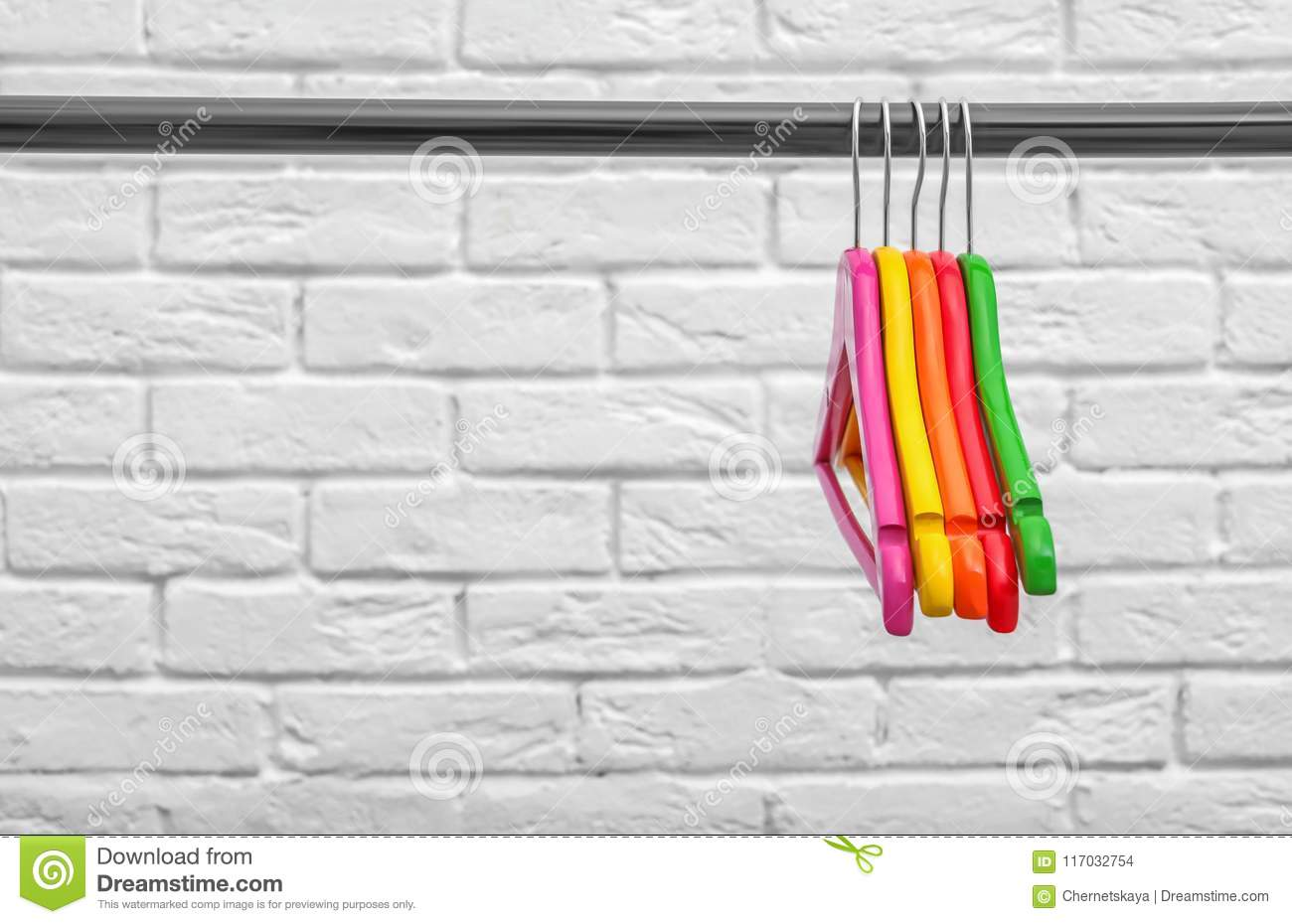 Clothes Hangers On Metal Rail Against Wall Background Stock
