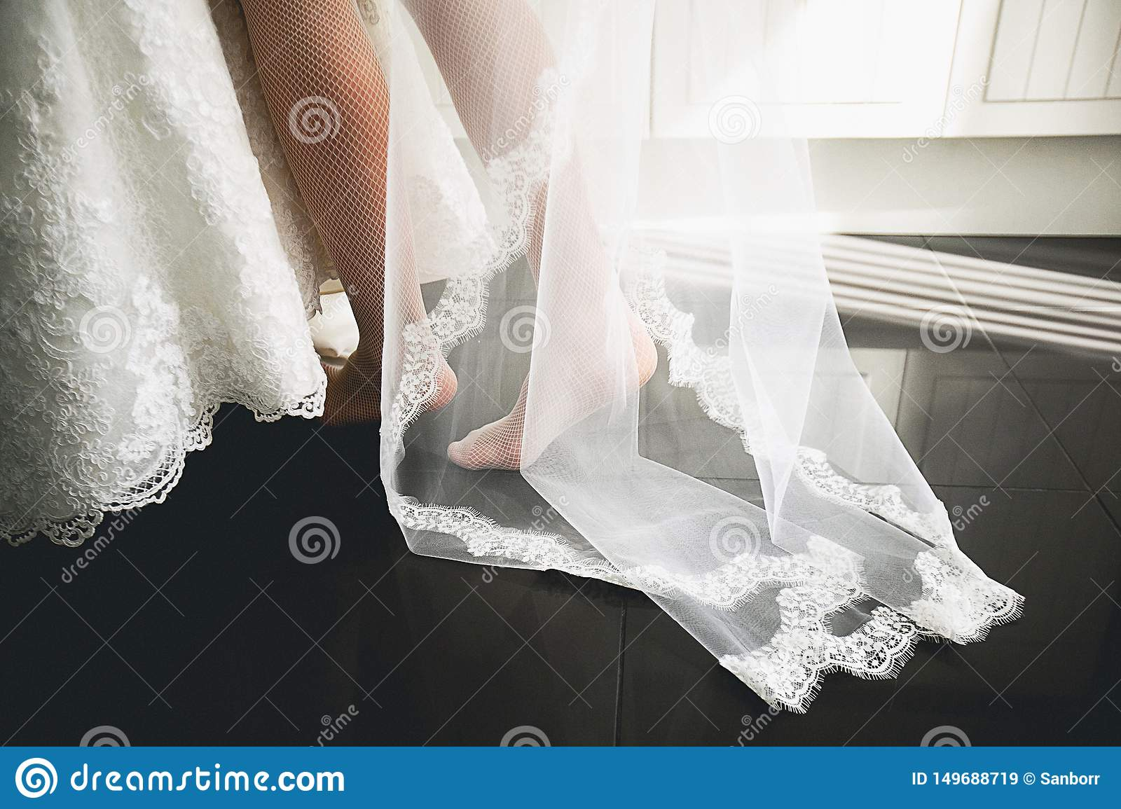 Clothes and legs of the bride close-up, against the black floor. A young woman takes a beautiful white openwork dress and a veil.