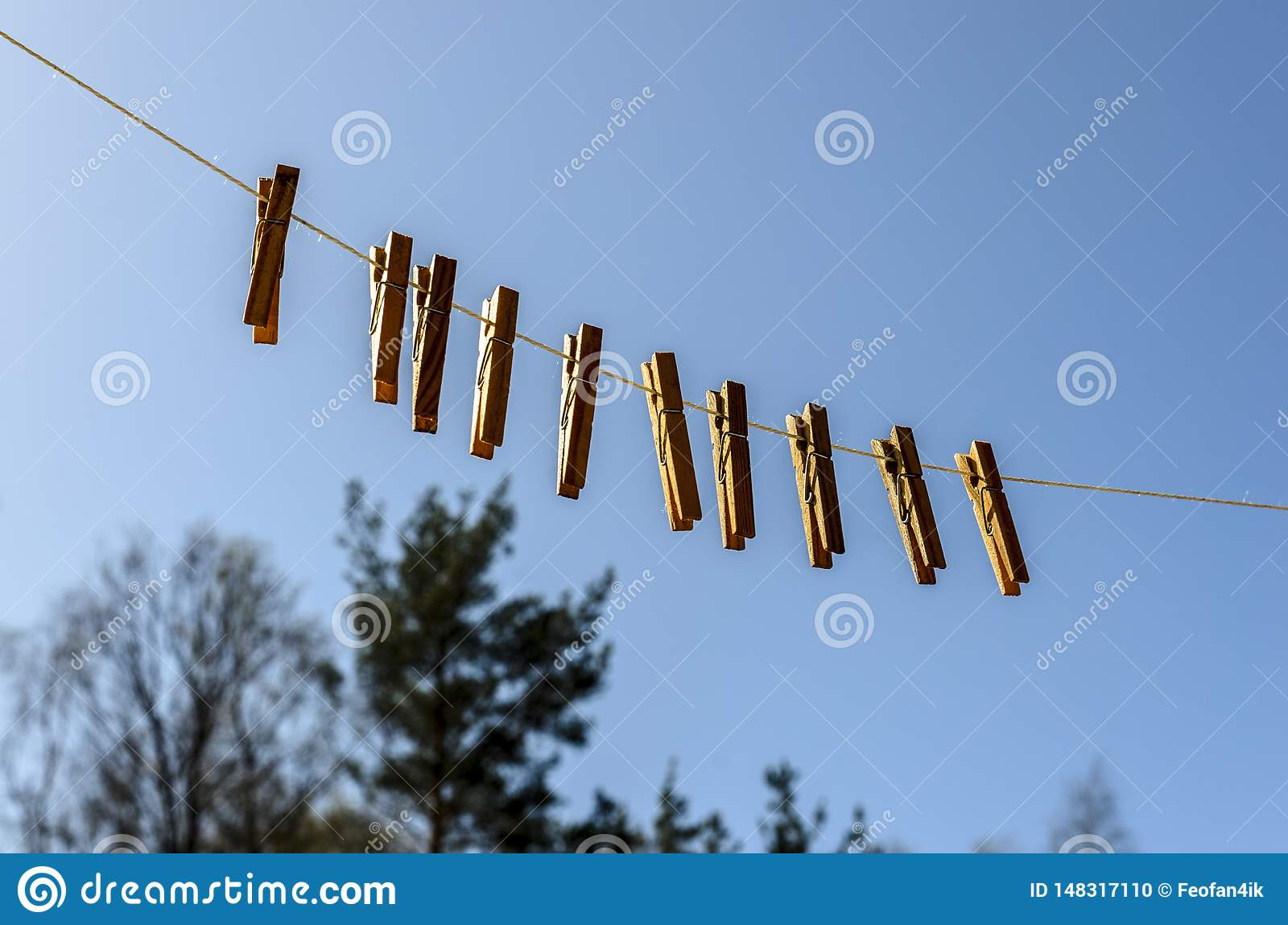 Clothespins for clothes and clothes hang against the blue sky on a Sunny day on a
