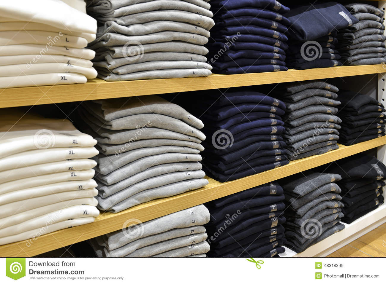Clothing stacked neatly on the shelf in fashion shop