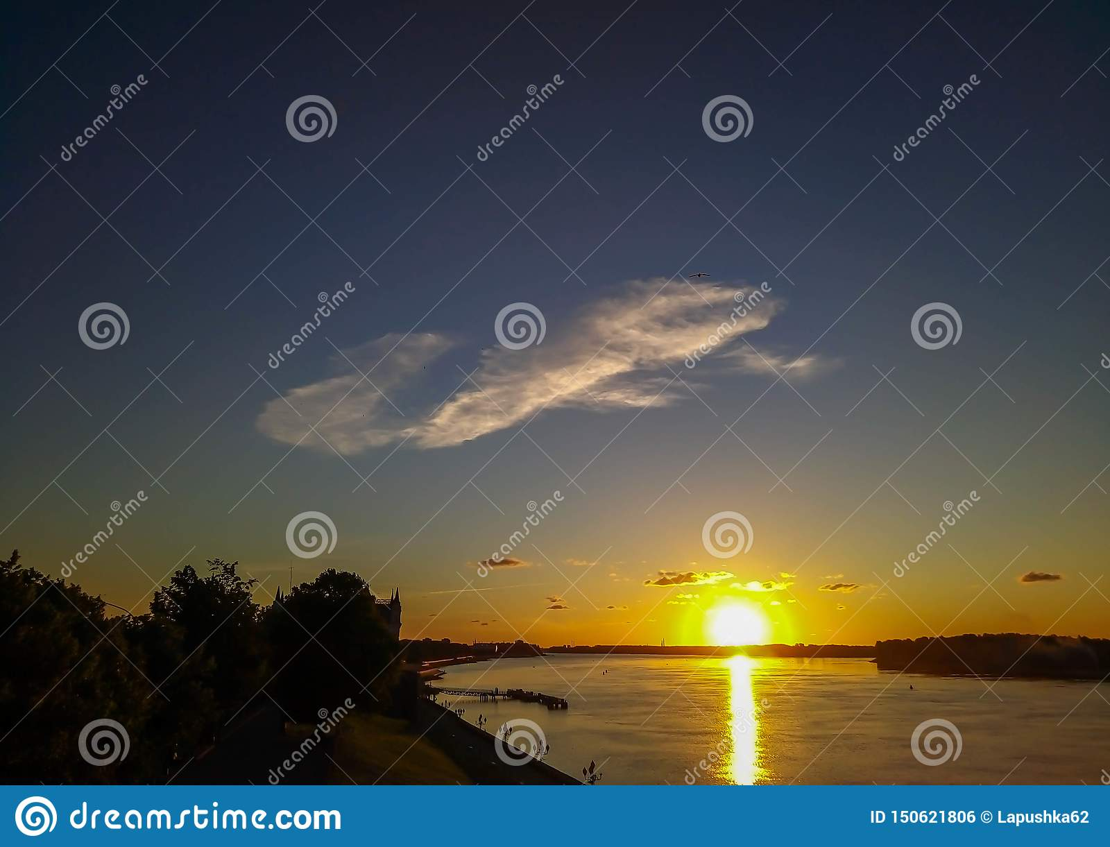 Cloud over the river in the rays of the sunset