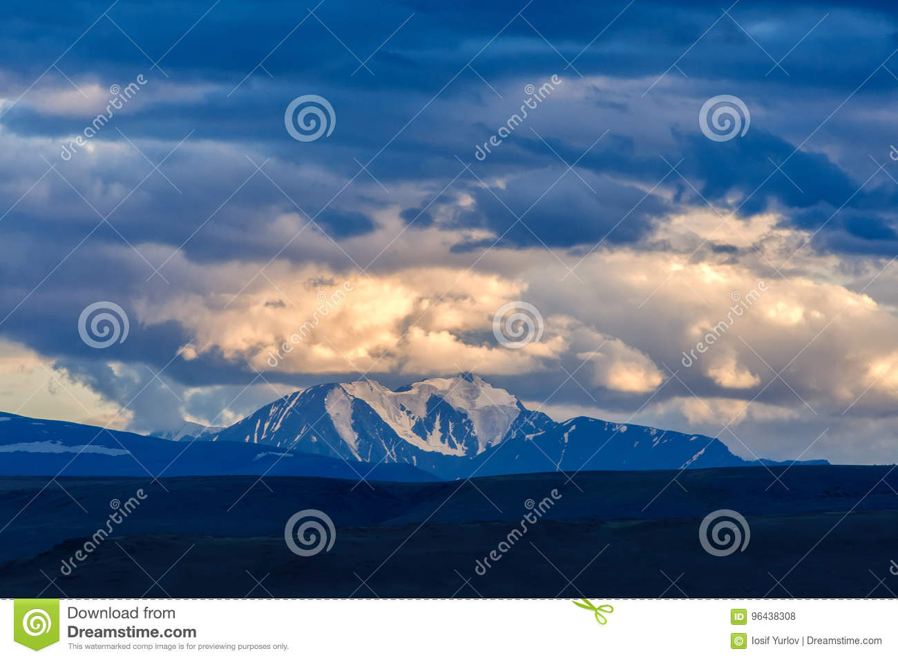Clouds passing over mountain pinnacle in sunset light