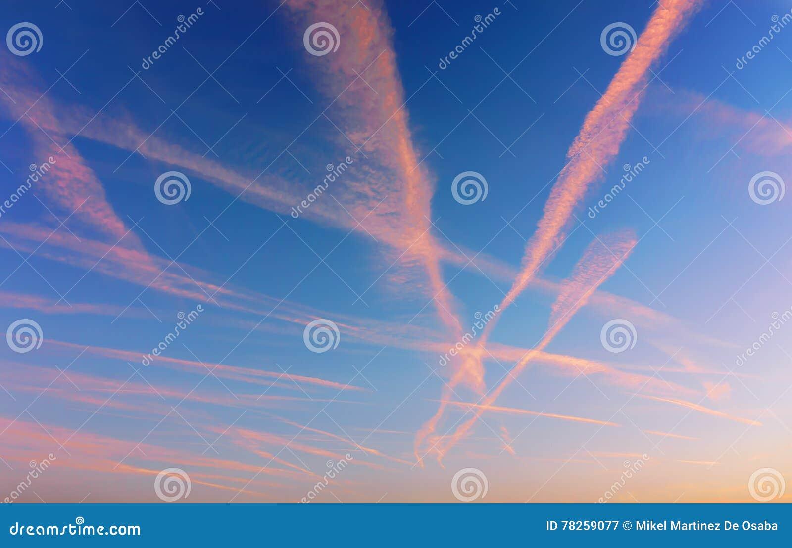 Cloudscape με τα ίχνη αεροπλάνων στο ηλιοβασίλεμα