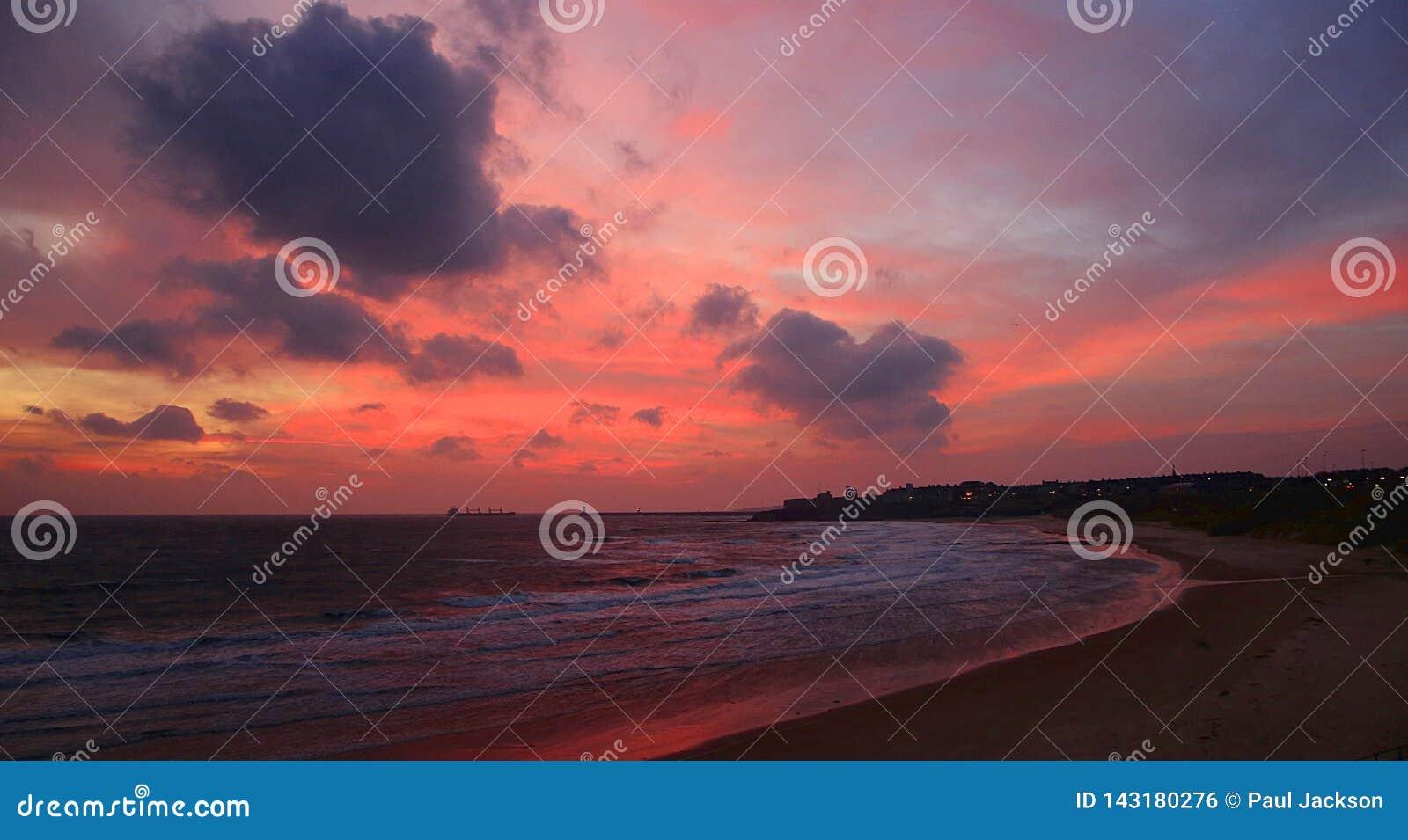 Cloudy, pink sunrise on Tynemouth Longsands beach