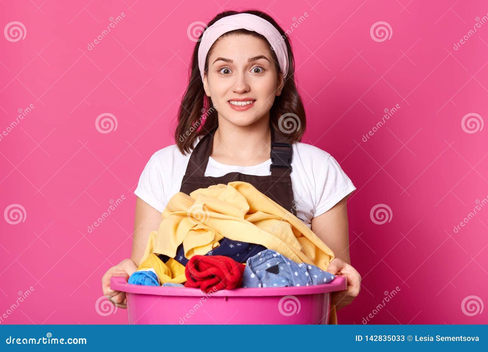 Clouse die omhoog van mooie huisvrouw, over huis werken, houdt reusachtig roze bassinhoogtepunt van vuil linnen, bekijkt verrast