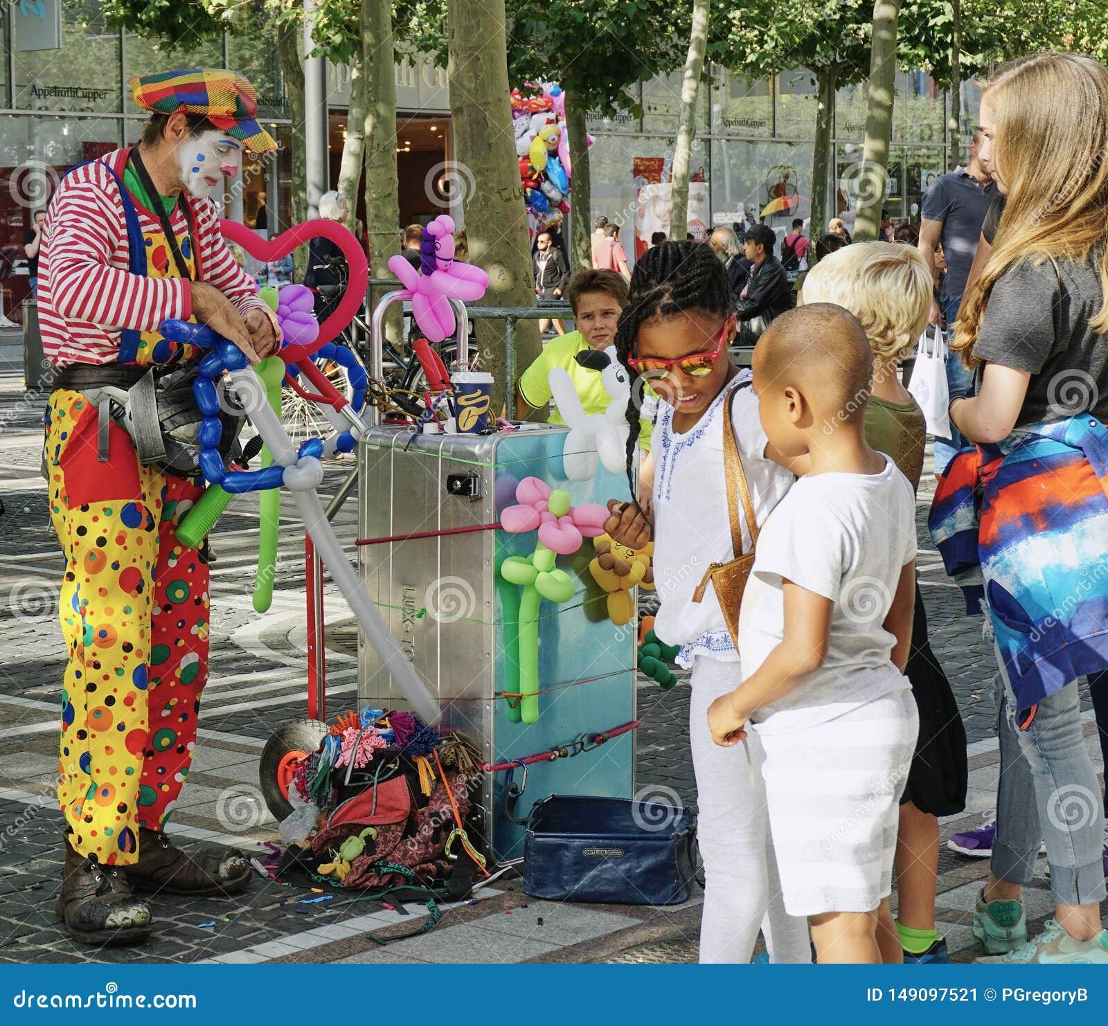 Clown Entertains Kids op de straat in Frankfurt, Duitsland