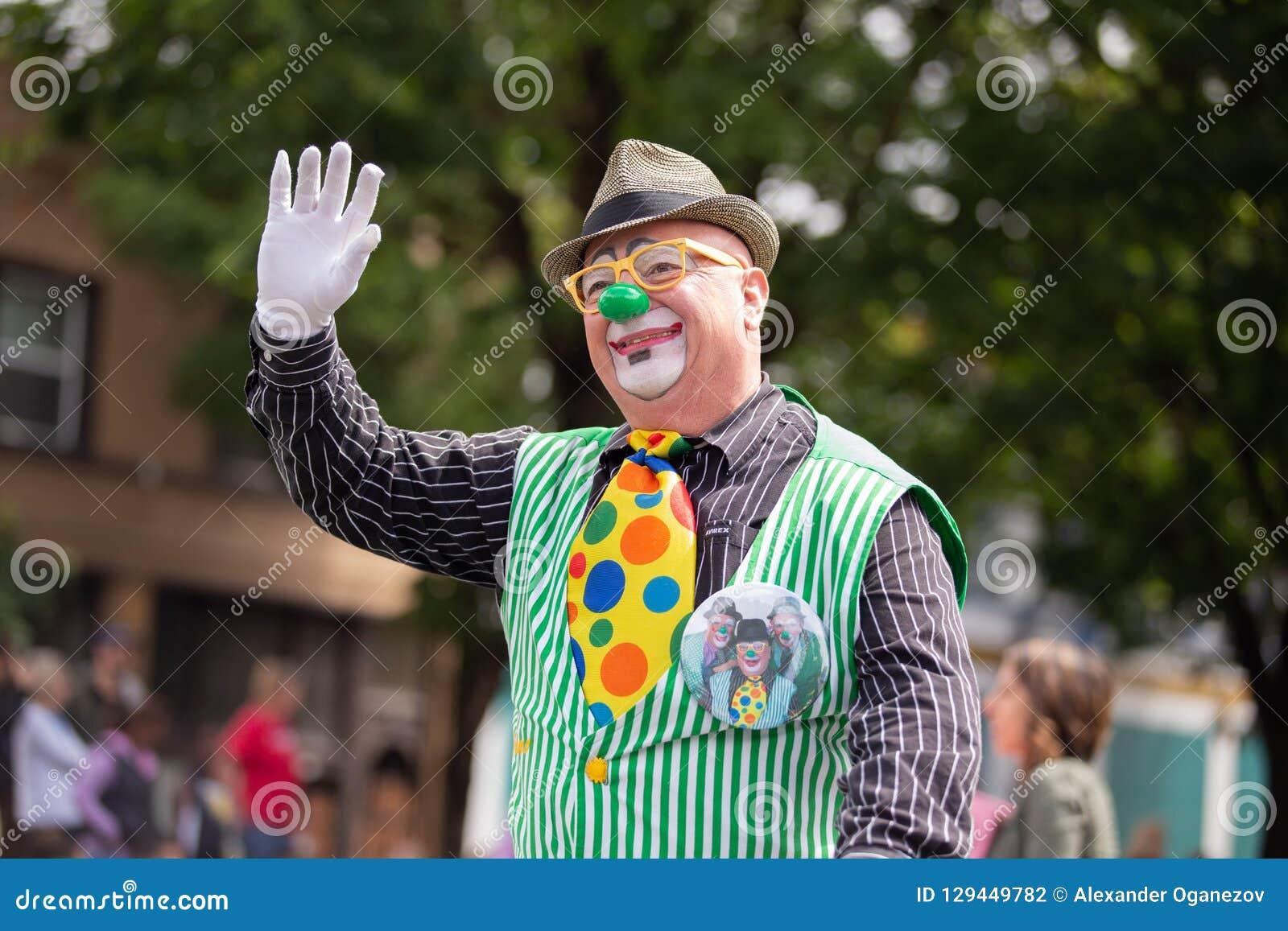 Clown na mão de ondulação verde do traje e do chapéu