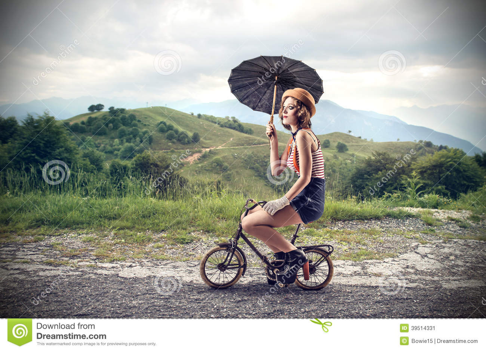 Clown riding a little bike with an umbrella