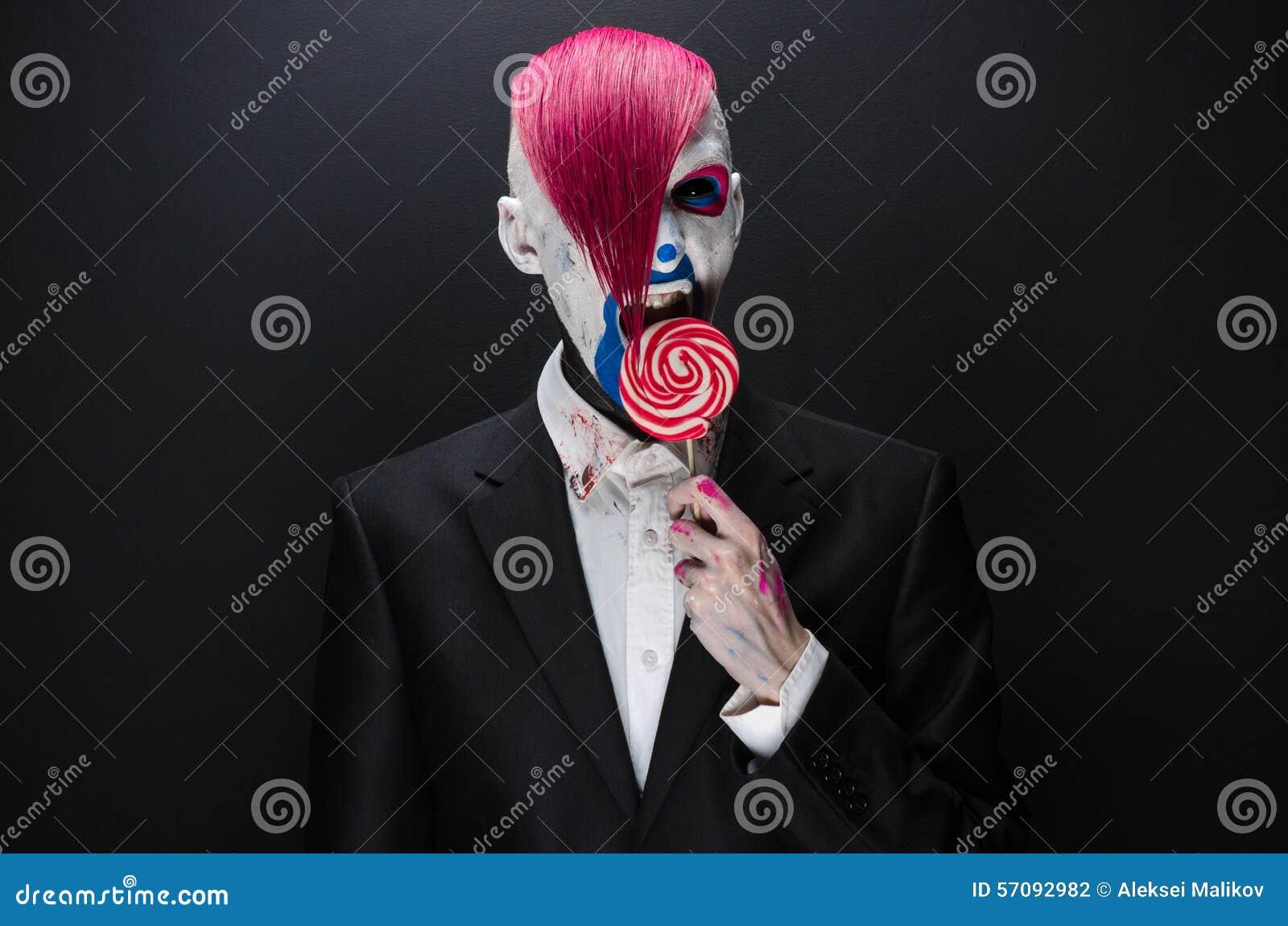 Clown- und Halloween-Thema: Furchtsamer Clown mit dem rosa Haar in einer schwarzen Jacke mit Süßigkeit in der Hand auf einem dunk