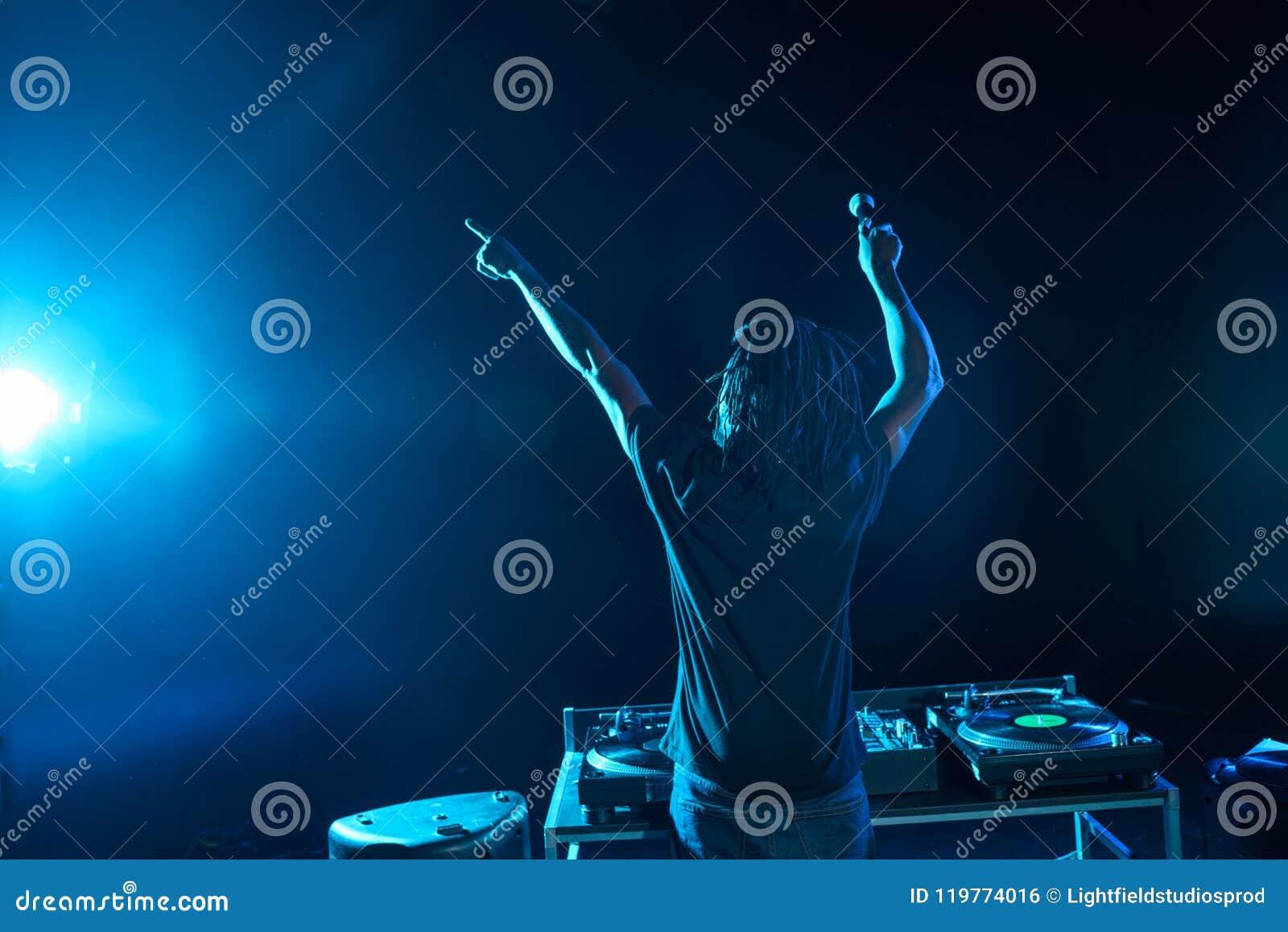 Club afroamericano profesional DJ con el mezclador de sonidos en concierto