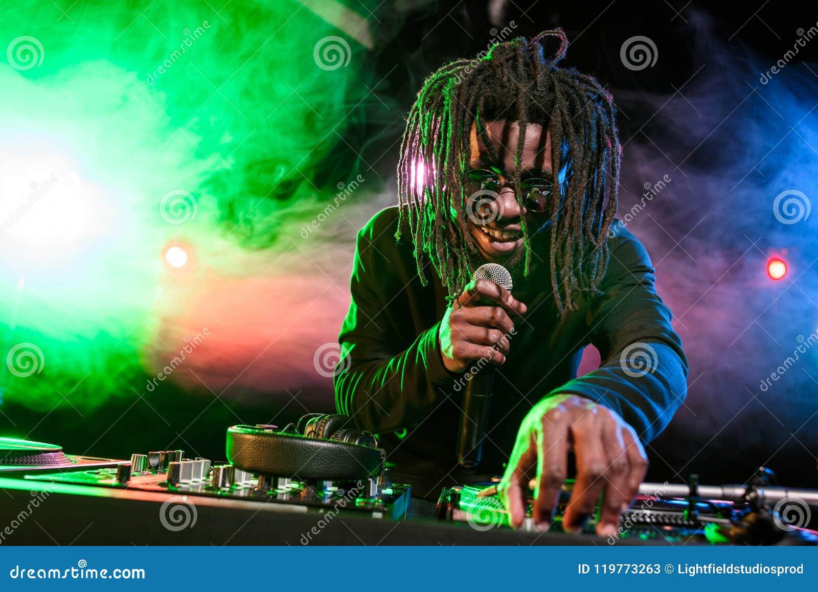 Club afroamericano profesional DJ con el mezclador del micrófono y de sonidos