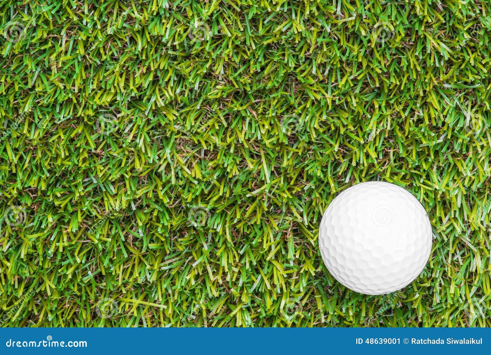 Club de golf y bola en hierba