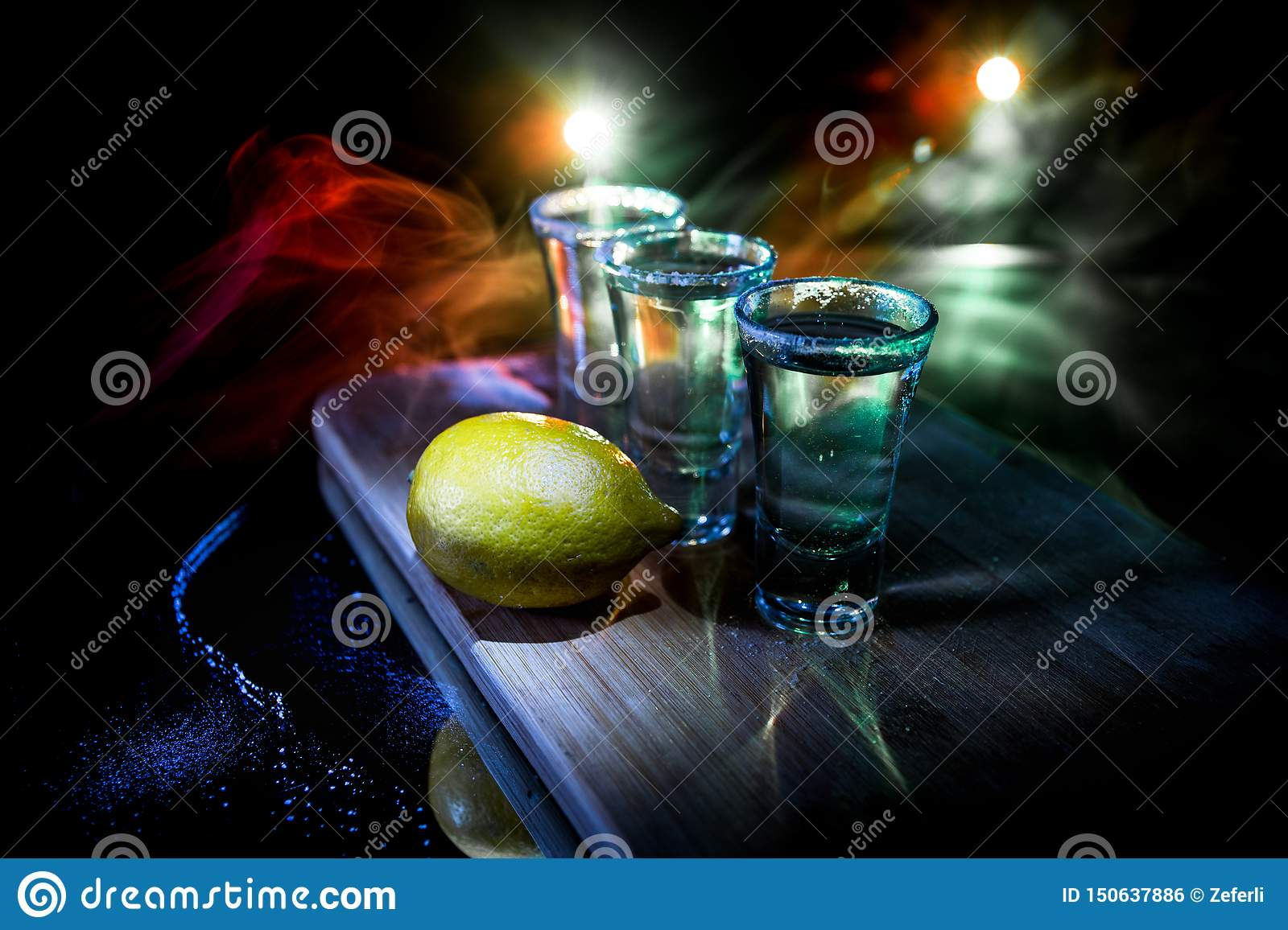 Club drink concept. Tasty alcohol drink cocktail tequila with lime and salt on vibrant dark background or glasses with tequila at
