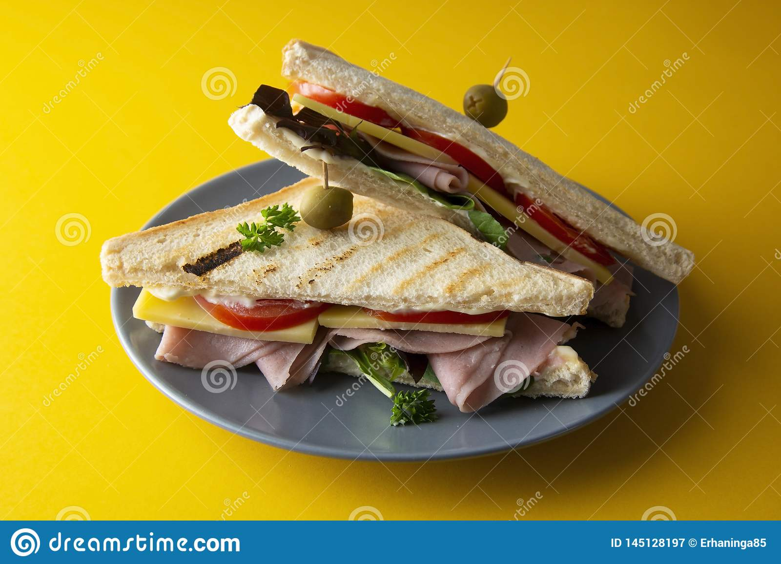 Club sandwich with ham isolated. Toasted double panini with ham, cheese fresh vegetables. Yellow background