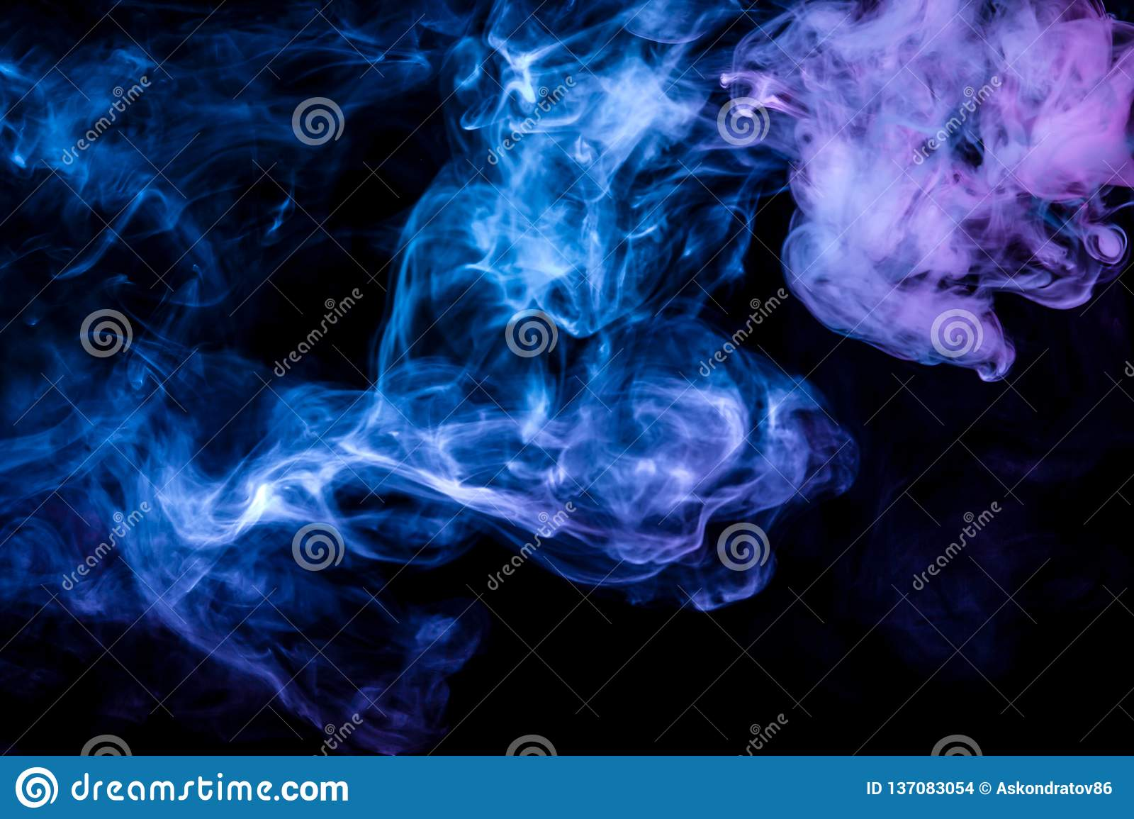 Clubs of colored smoke of blue and pink color on a black background in the form of soft clouds from vape